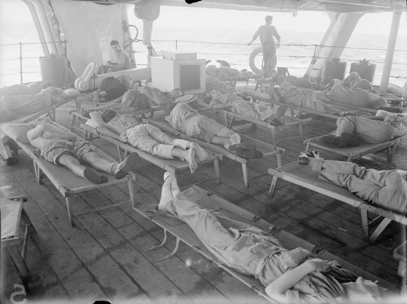Fleet Air Arm pilots and observers sleep on camp beds on the quarterdeck of HMS Illustrious to catch what cool sea air they can during the Andaman Island operation.