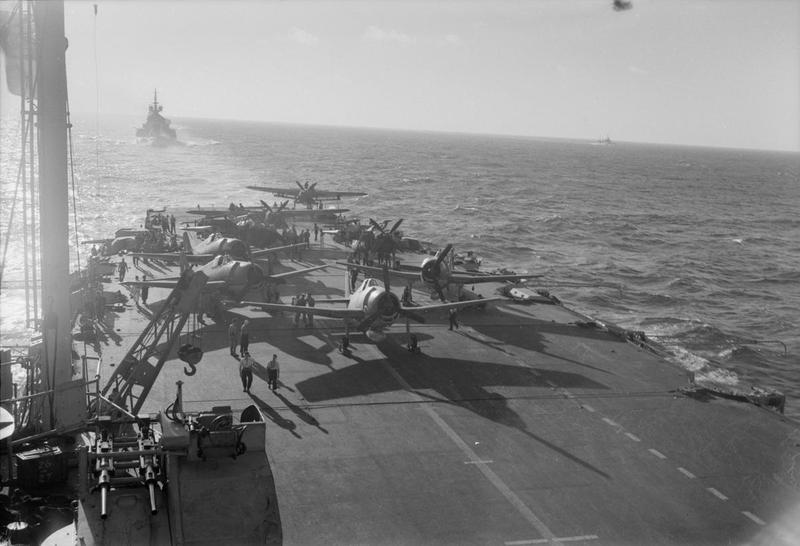 Fairey Barracudas and Grumman Hellcats being ranged on the flight deck of HMS INDOMITABLE as the sun goes down. HMS HOWE is astern.