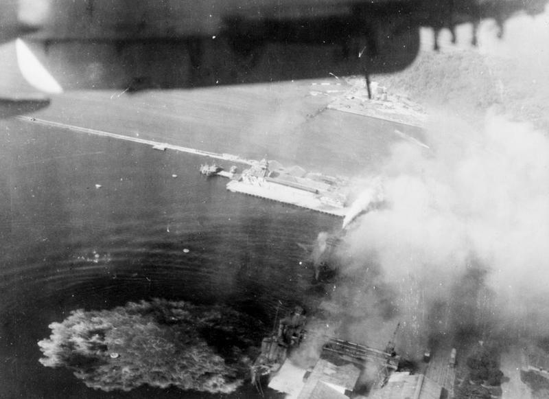 A stick of bombs bursting on 3,500 ton Japanese supply ship during the surprise attack on Emmahaven, the port of Padang. Four direct hits were obtained on the ship. Hits can also be seen on a 2,500 ton supply vessel lying astern, and both vessels were left burning fiercely.