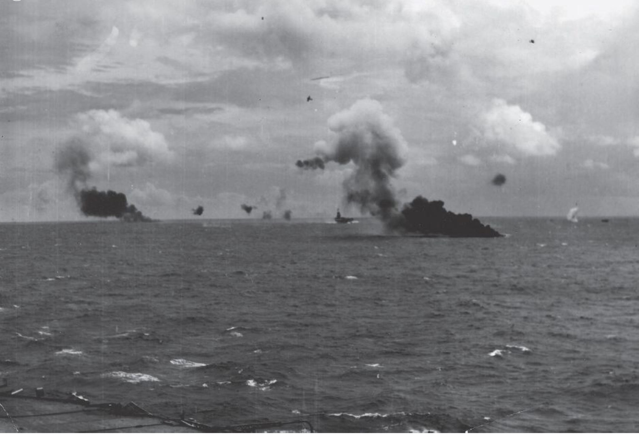 "The remains of two Japanese ""Sally"" bombers burn on the water as a third skims the waves just below the horizon (far right) after a Seafire pulls away from its attack (centre top)."