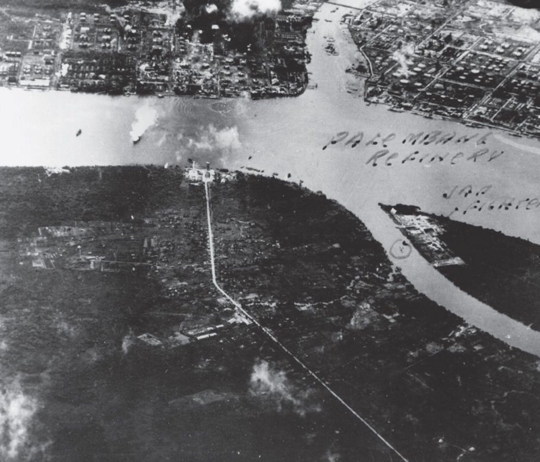 This photograph, taken by Air Coordinator Major Hay during the Meridian II attack on Songei Gerong, has been marked by analysts to highlight the presence of a Japanese fighter. The refinery can be seen burning in the top-left of the image, and the tanker on the left.