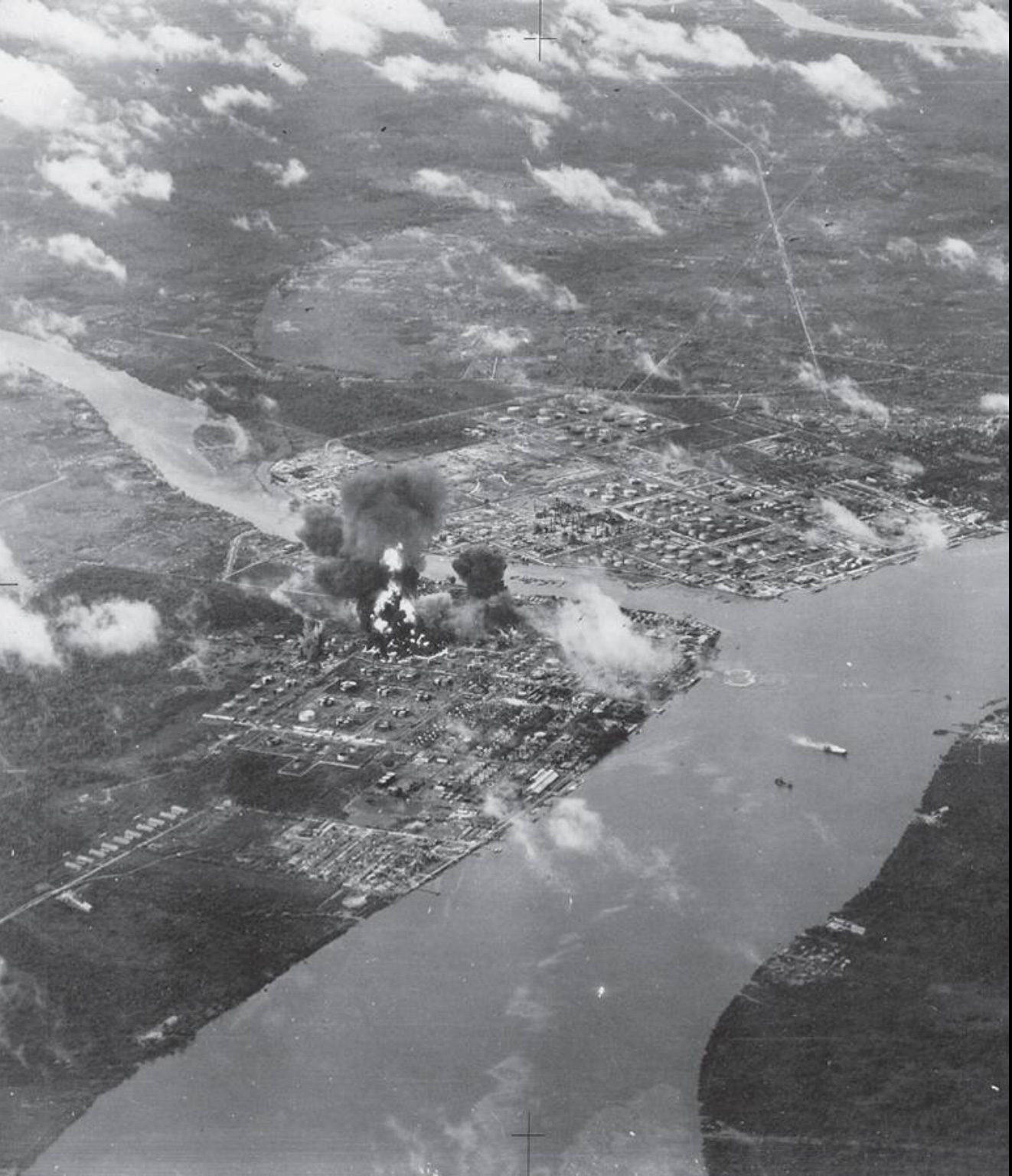 This reconnaisance photo taken from Major Hay's Corsair shows bombs bursting within Songei Gerong refinery during Operation Meridian II. A tanker is burning in the river, middle-right.