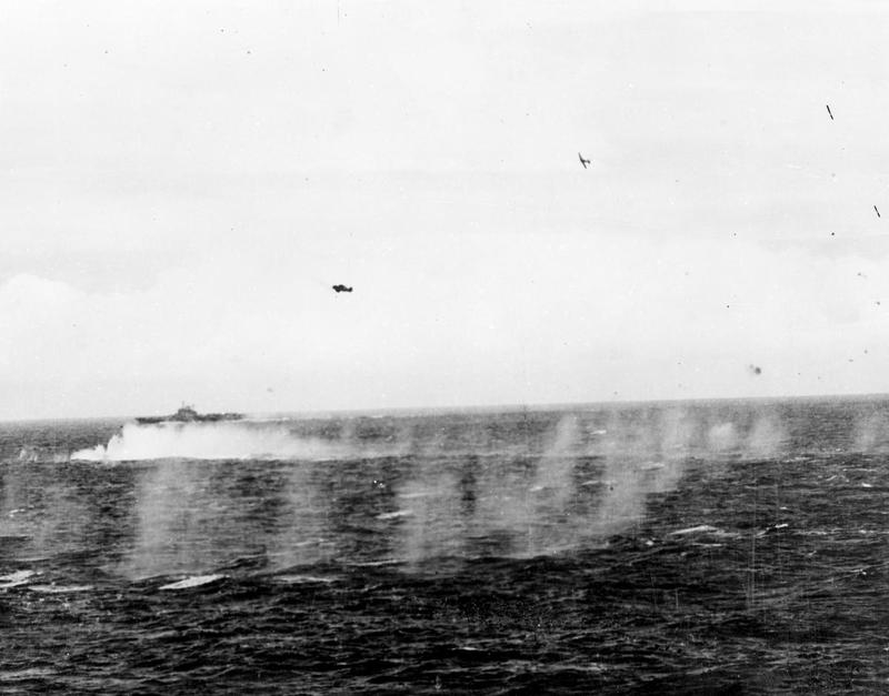A Seafire (top right) having shot down a Japanese aircraft (middle left) turns away as an Avenger prepares to land on its carrier in the aftermath of Meridian II.
