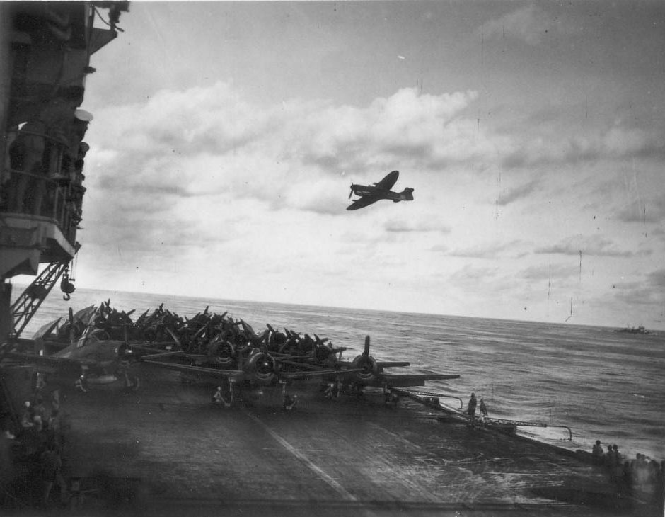 A Firefly from HMS INDEFATIGABLE passes over HMS INDOMITABLE which has a range of Hellcats and Avengers ready for launch.