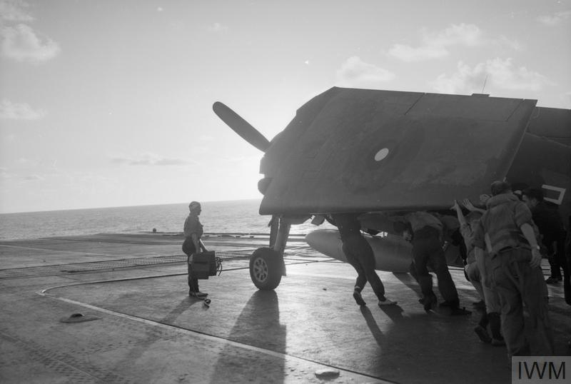 A Hellcat aboard HMS INDOMITABLE is ranged on deck as dawn breaks.