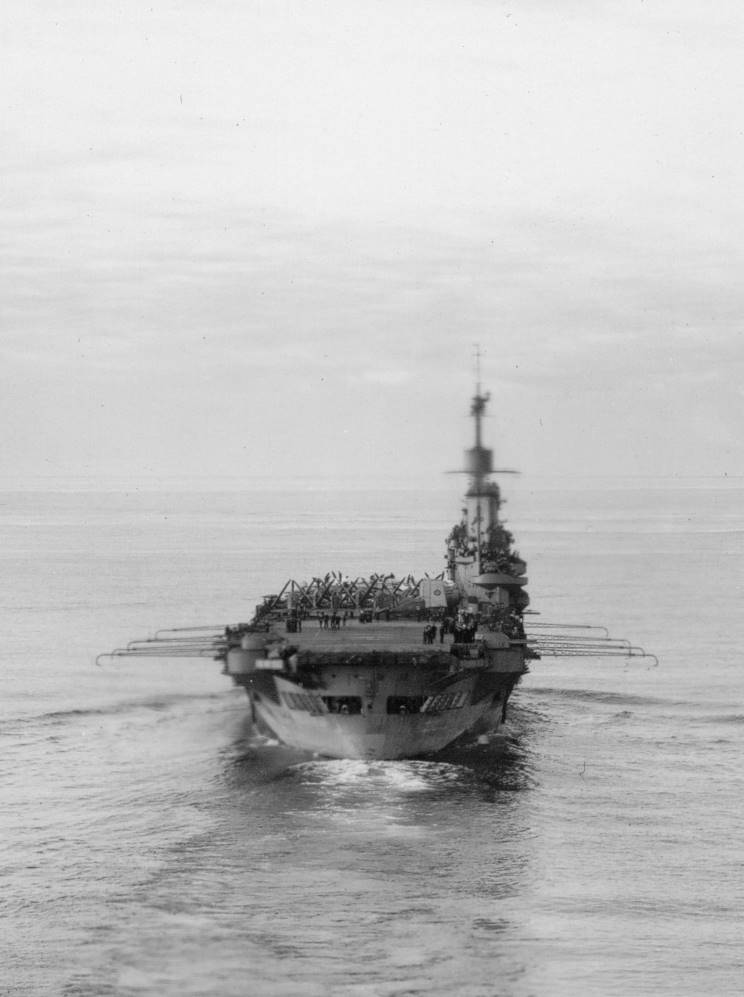 HMS ILLUSTRIOUS, with her deck park crowded amidships.