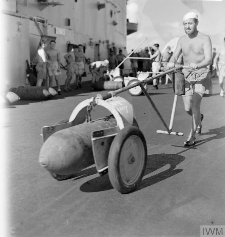 Steward K Mallinder, of Sheffield, wheeling a 500 pounder during bombing up on an Eastern Fleet armoured carrier, 1944. In the background left deck crew can be seen standing around the bomb hoist chute in the main island, with more 500lb weapons on the deck.