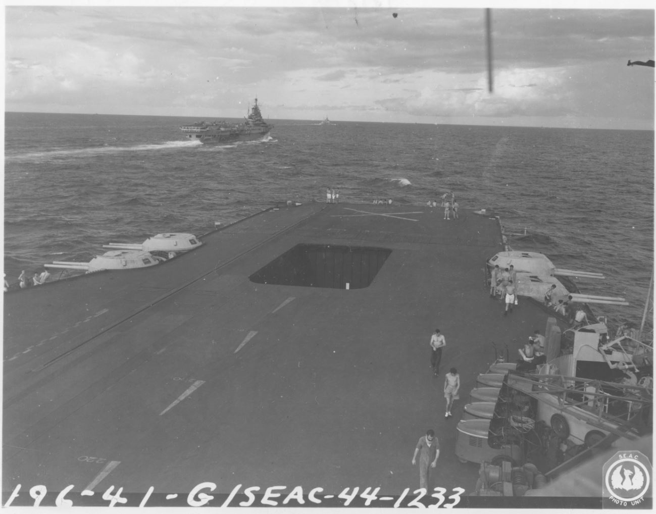 "Aboard the aircraft carrier HMS ""ILLUSTRIOUS""... HMS INDOMITABLE taken from ""Admiral's Platform"" on HMS ILLUSTRIOUS. Cruiser HMS Newcastle in the background. Fleet is on way back to Trincomalee Ceylon. SEAC photo unit (US). Photographer: PFC Russell Scott. December 16 thru 23, 1944."