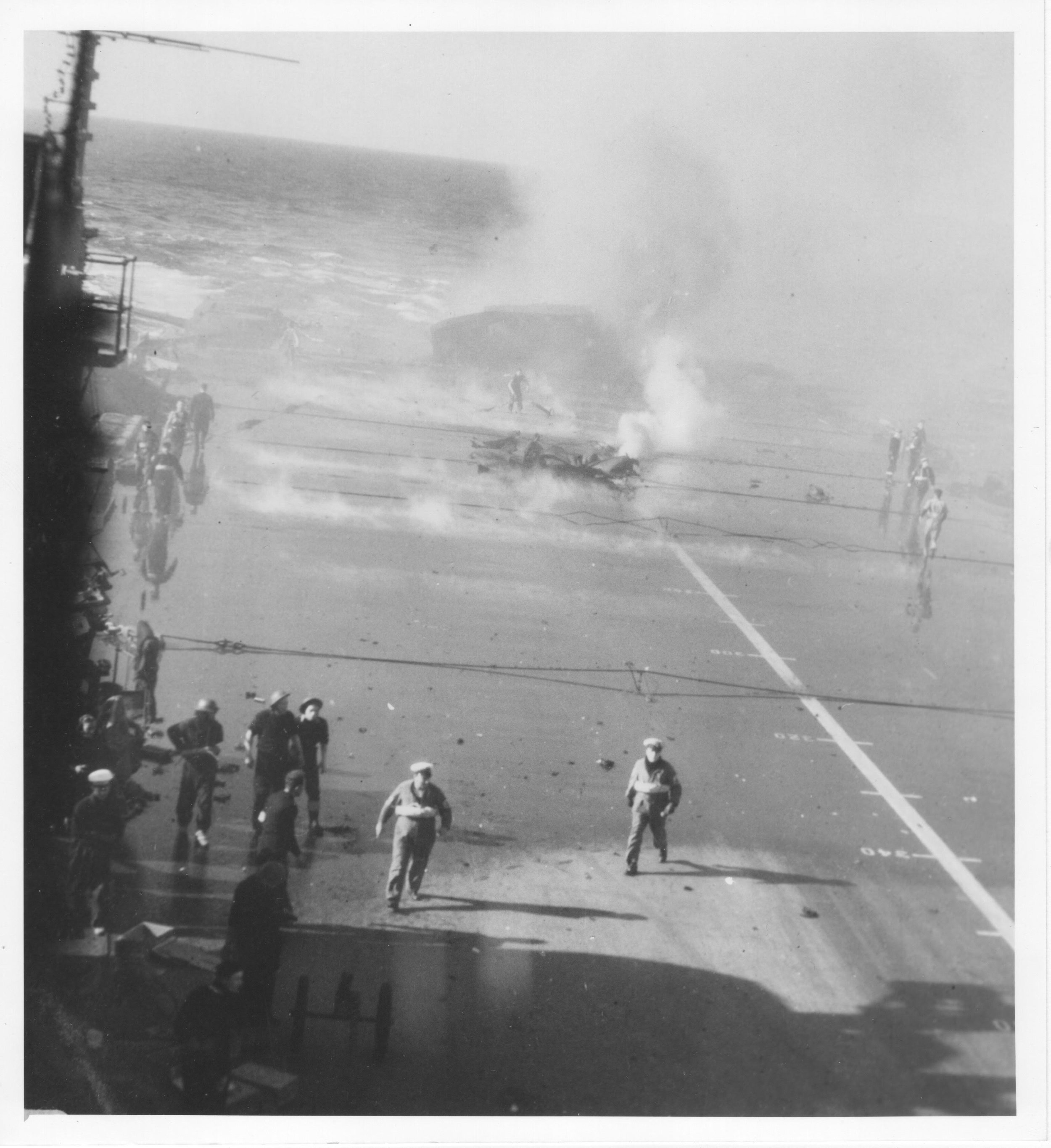 Puncture wound ... A snake of smoke curls out of the 19-22in hole in the 3in armoured portion of Illustrious' flight deck as the hardened steel steams from the inferno in the hangar below. The toppled aft lift at the rear is also venting thick smoke and steam.  Click on the image for a full-resolution view. Picture courtesy John Clark