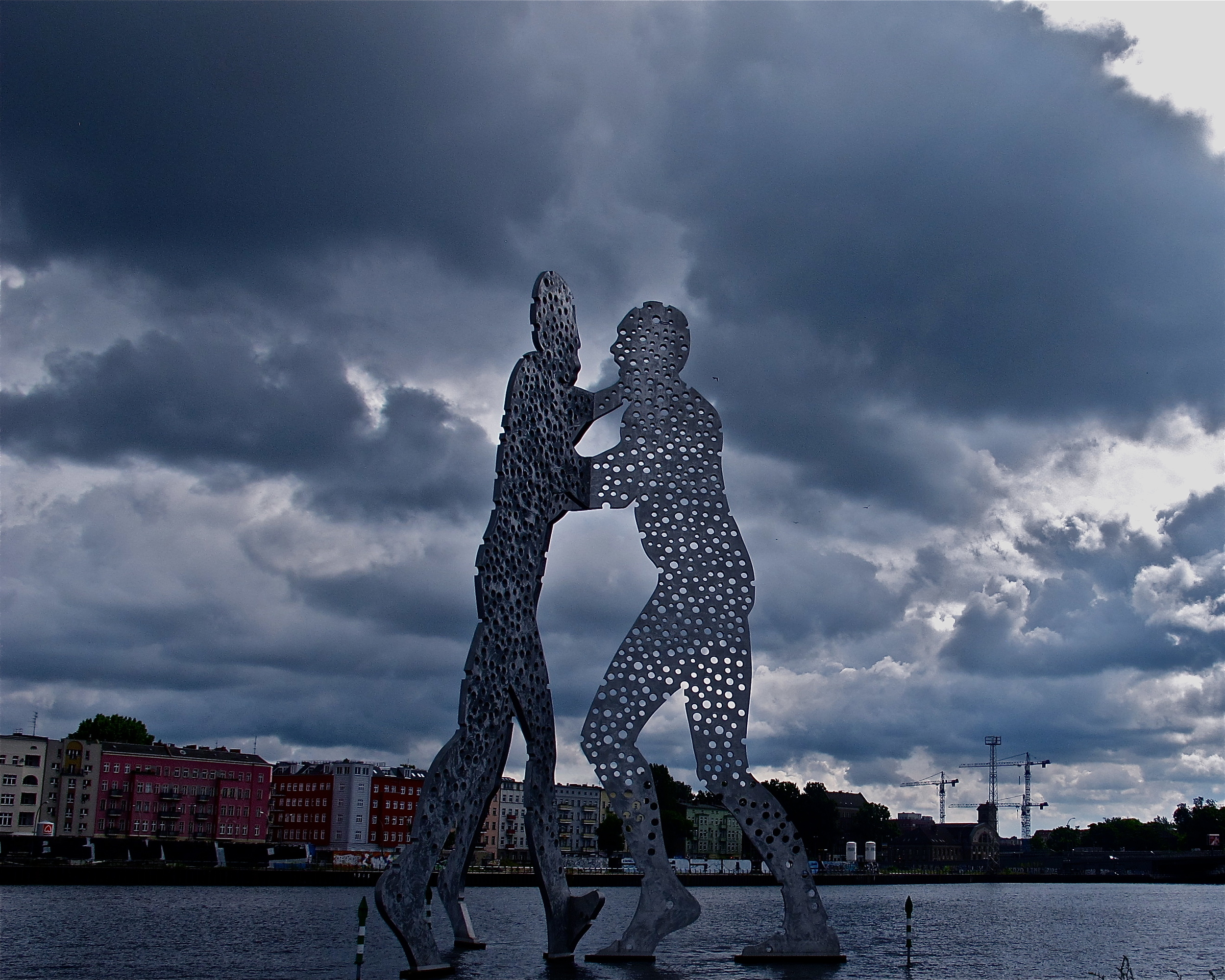 """MOLECULE MAN,"" BERLIN   American sculptor Jonathan Borofsky placed these 90-feet high figures in the River Spree, in Berlin. The day I was there, the clouds added to the mood of huge men wrestling for control -- an illusion to East Berliny/West Berlin?"