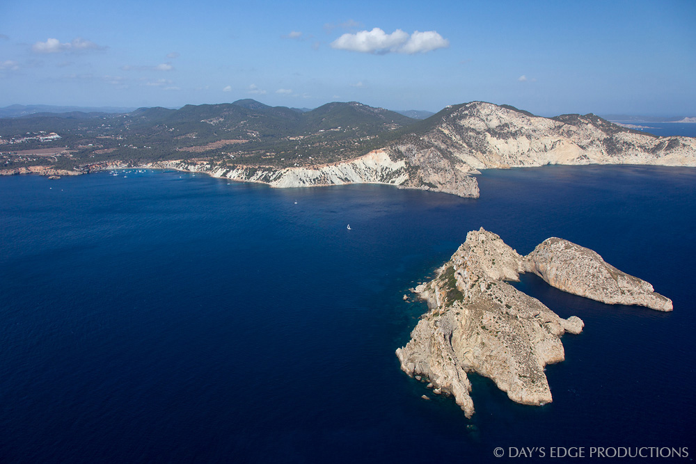 From the summit of Illa Es Vedrà, Illa Es Vedranell (foreground) and Ibiza (background) are visible. Photographed in Spain's Balearic Islands.