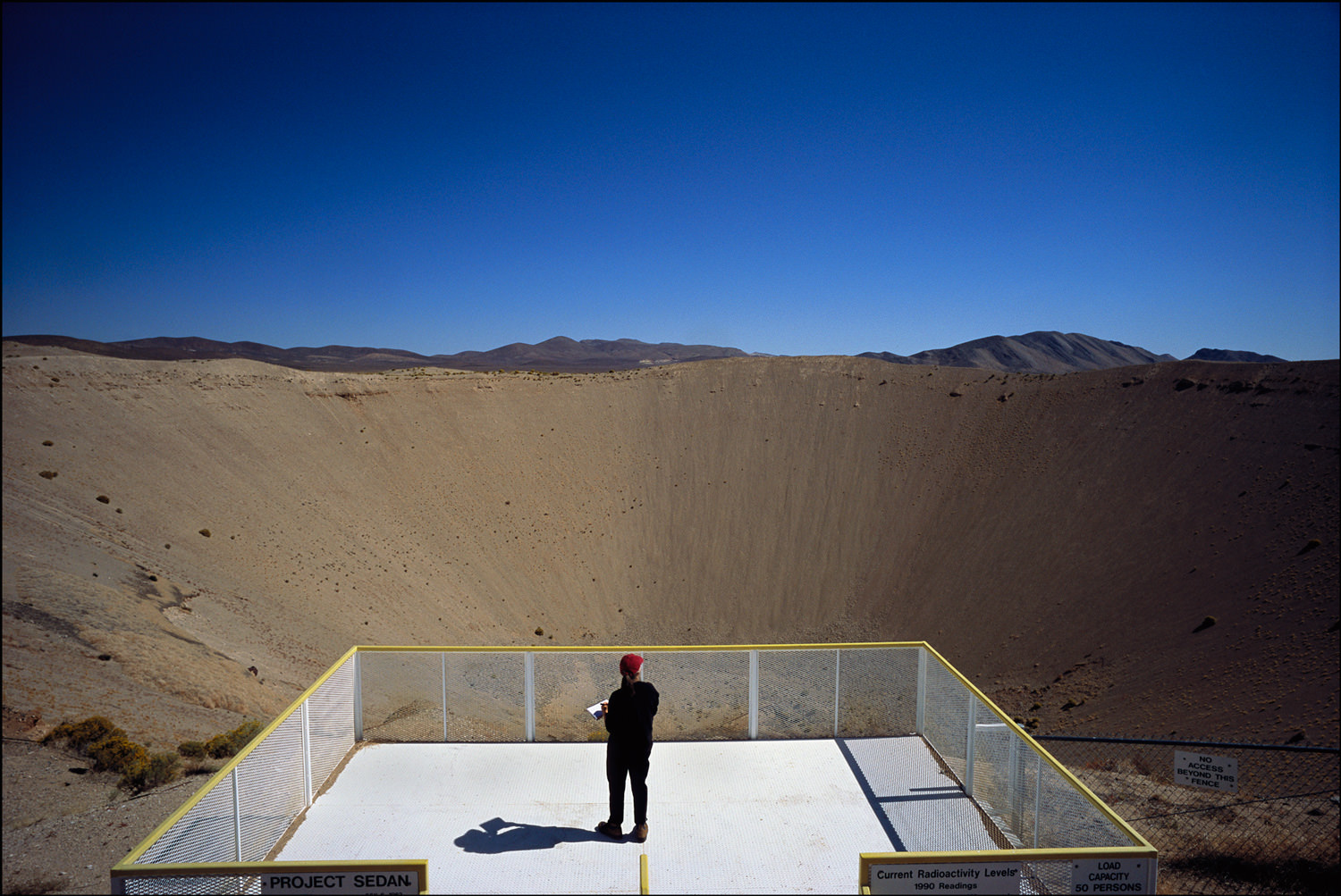 Judith Vollmer, poet and teacher, has come to Sedan Crater on the Nevada Test Site to better understand the loss of her father to radiation related illnesses.