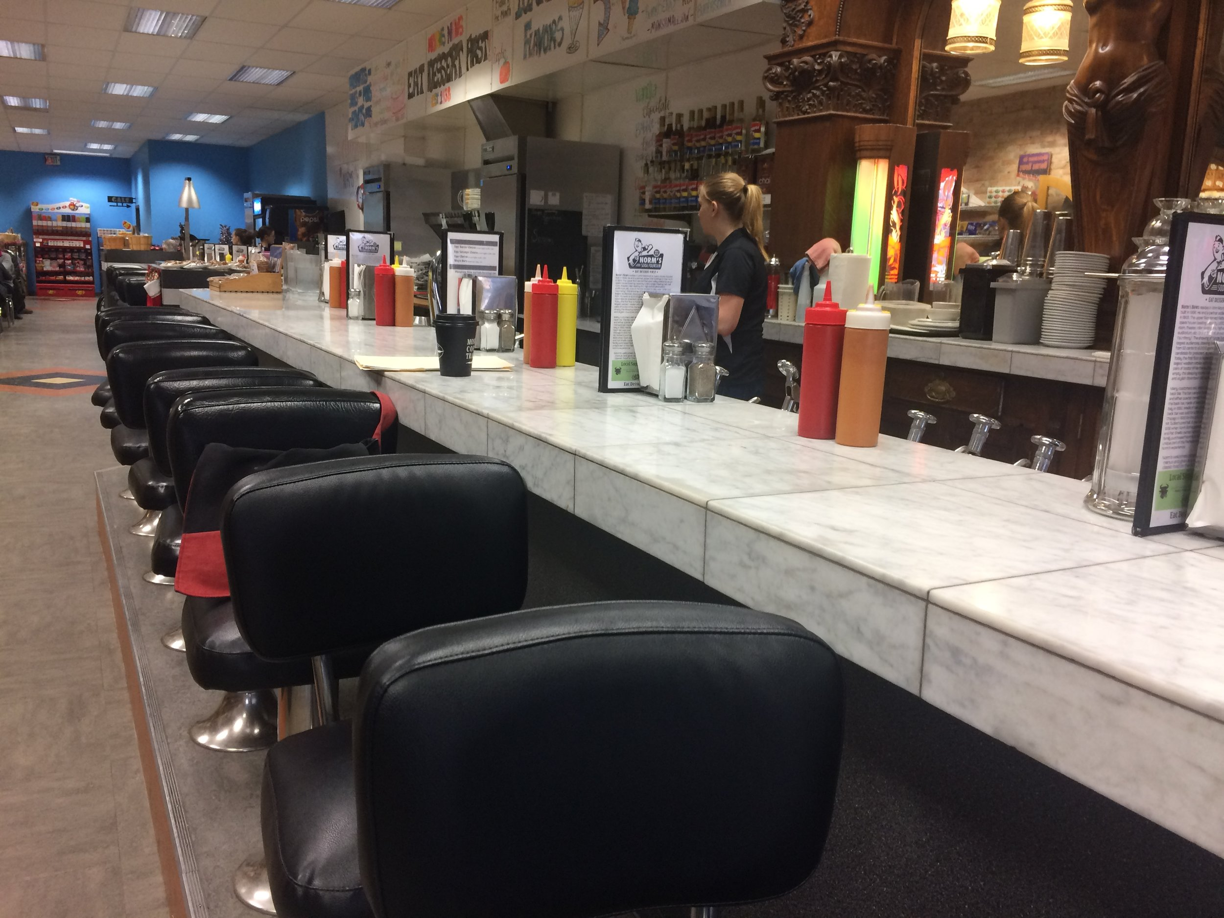 """The soda fountain at the McIntosh Opera opened in 1938 when Norm Schappeaker bought Mr. Tucker's Pool Hall. The beautiful oak and cypress """"Los Angeles"""" style Brunswick back bar had originally cost $369 in 1902. It was shipped to Kalispell in 1930 from Chicago at a cost of $3000."""