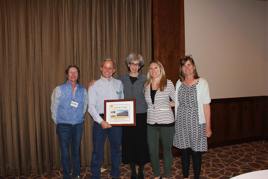 CTA team members accepting the award for an Outstanding Commercial Rehabilitation with Stephanie Ambrose-Tubbs (left) and Chere Jiusto (right)