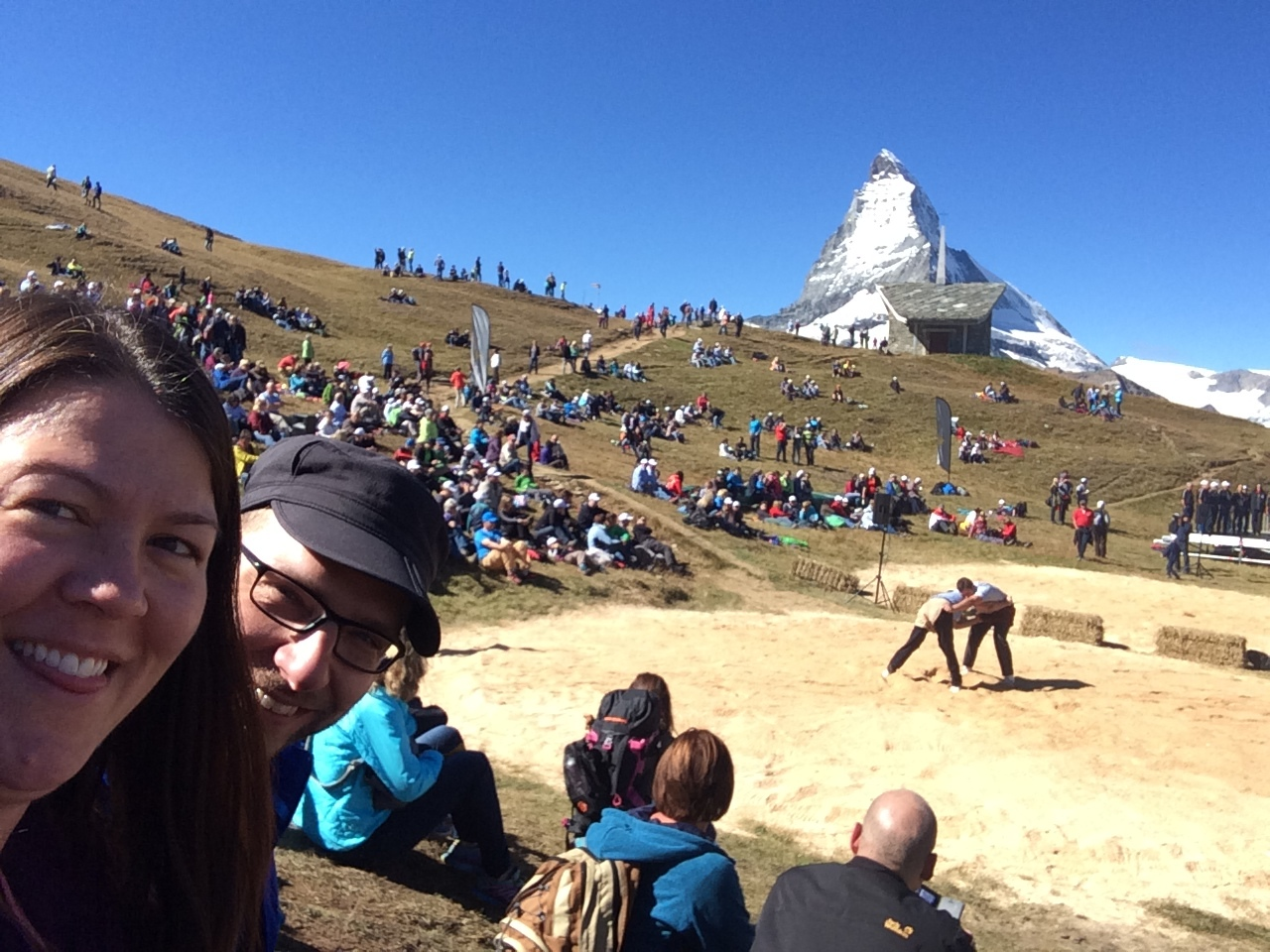There is a lot going on in this picture. First, it's a picture of the Matterhorn. Second, it's a picture of a traditional Swiss pass-time, Schwingen. Lastly, it's a picture of people, primarily Swss, watching Swiss Schwingen..