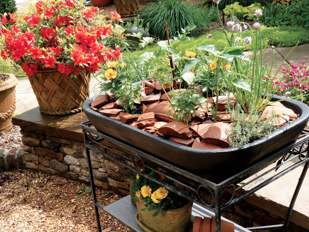 Our small self-watering planter fits right inside the frame of an old metal table. We also used broken pieces of terracotta as mulch.
