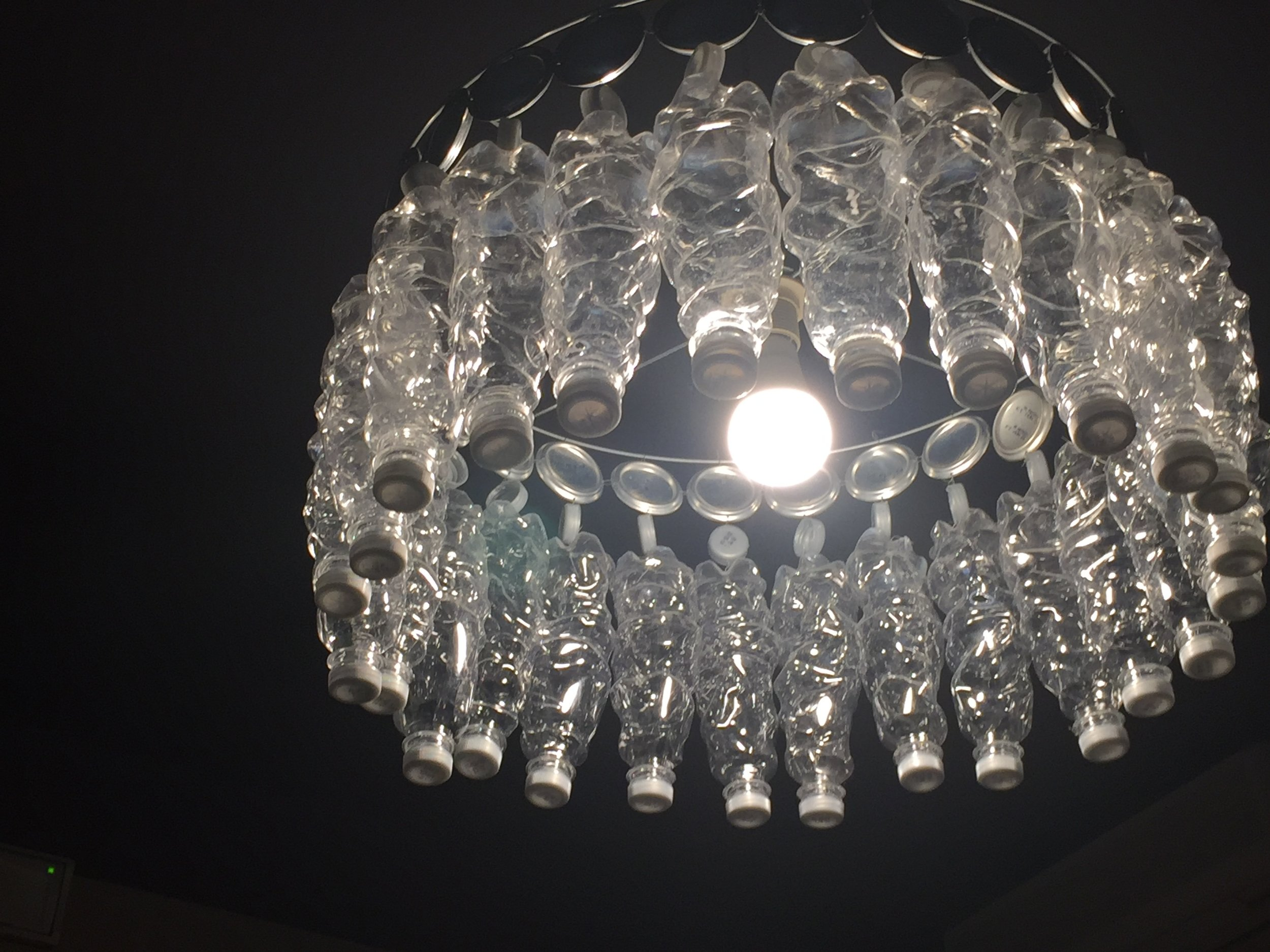 """The """"chandelier"""" in our room. Look closely- see the water bottles, tops and metal bottom of cans? (I apologize, I couldn't edit the size of this picture.)"""
