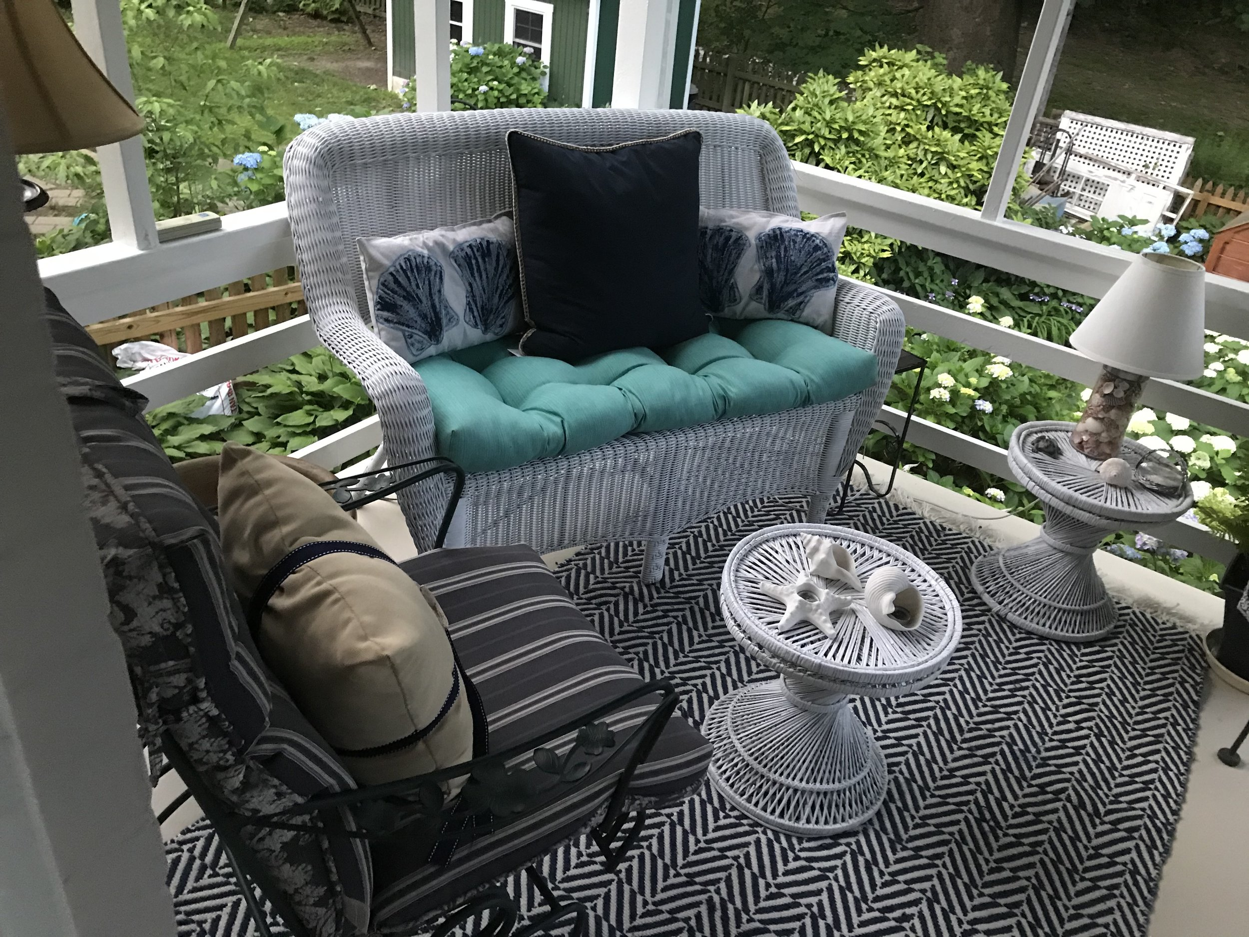 Our screened porch (sans screening-a summer project in the wings) with my hand painted scallop pillows.