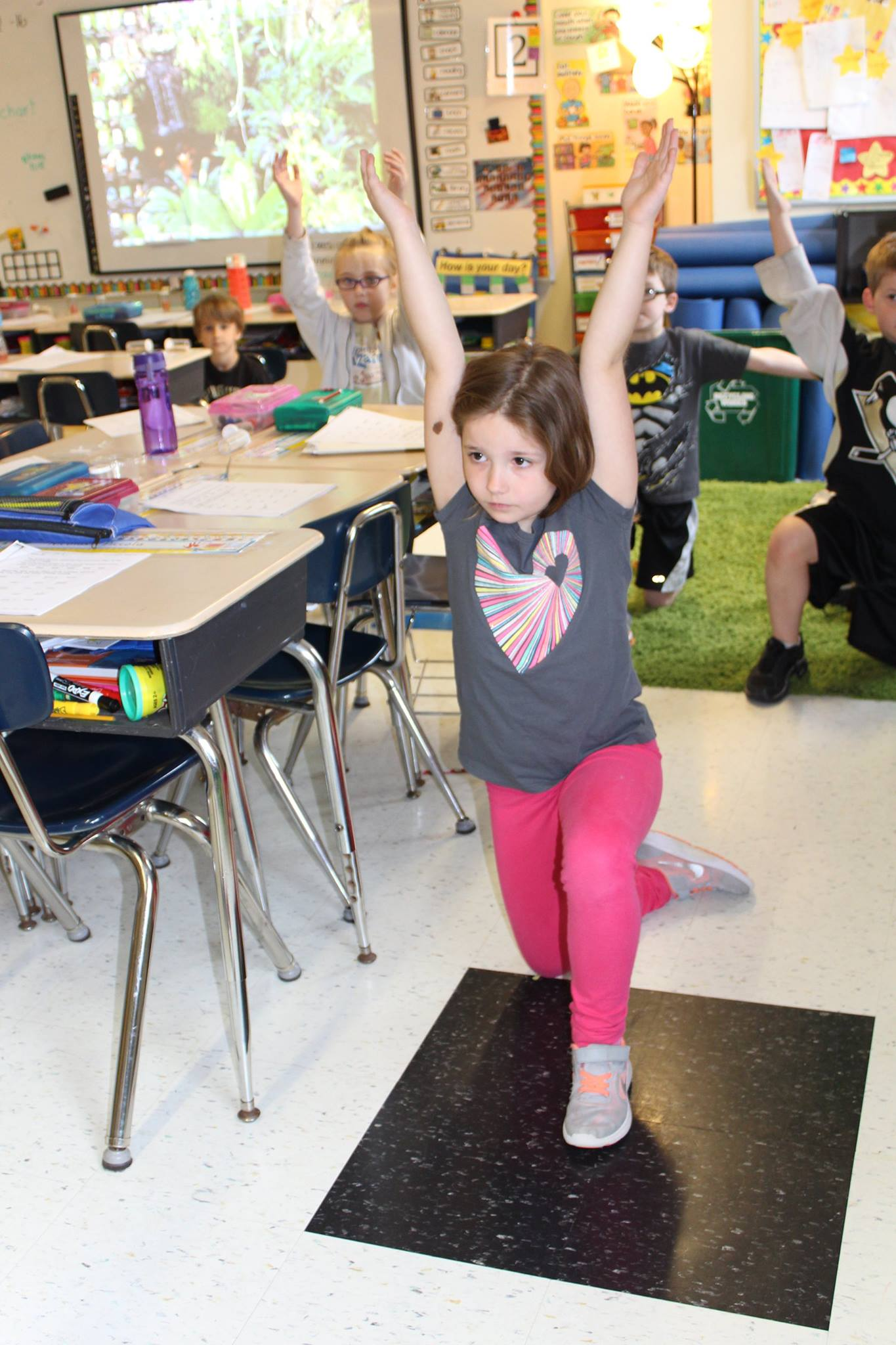 The kids doing yoga in the classroom.