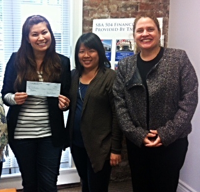 Kelly receives her loan check from Working Solutions Lending Director Agnes & CEO Emily