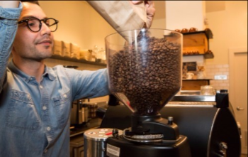 Owner Rafael Vizcaino pours coffee beans at Chapel Hill Coffee Co. on COMMERCIAL Street