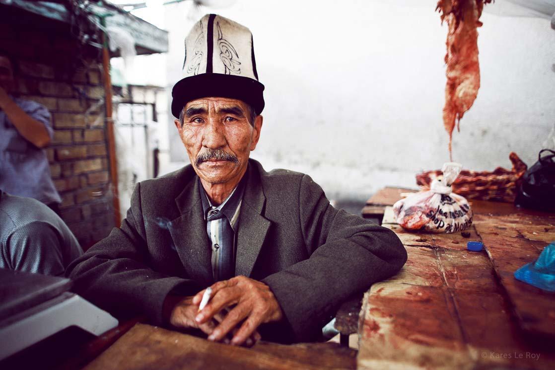 Kyrgyz butcher in Osh Bazaar. He wears the traditional felt hat: Ak-Kalpak / Boucher kirghize au bazaar de Osh. Il est coiffé du  chapeau traditionnel en feutre  | KYRGYZSTAN