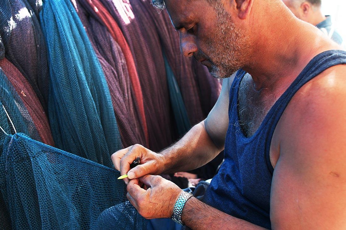 A fisherman mending his net in  Sinop  harbor| TURKEY