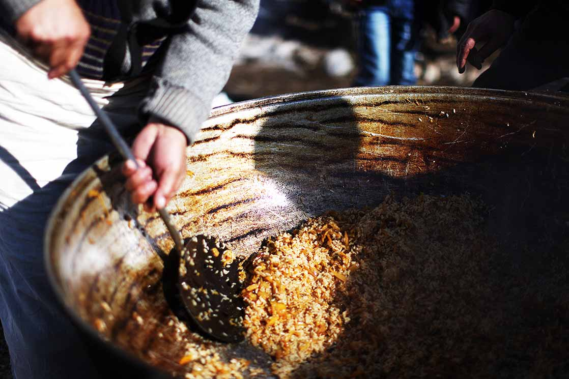 A giant  Plov , a cult dish of Central Asia,  in which rice is cooked with carrot and garlic  | KYRGYZSTAN