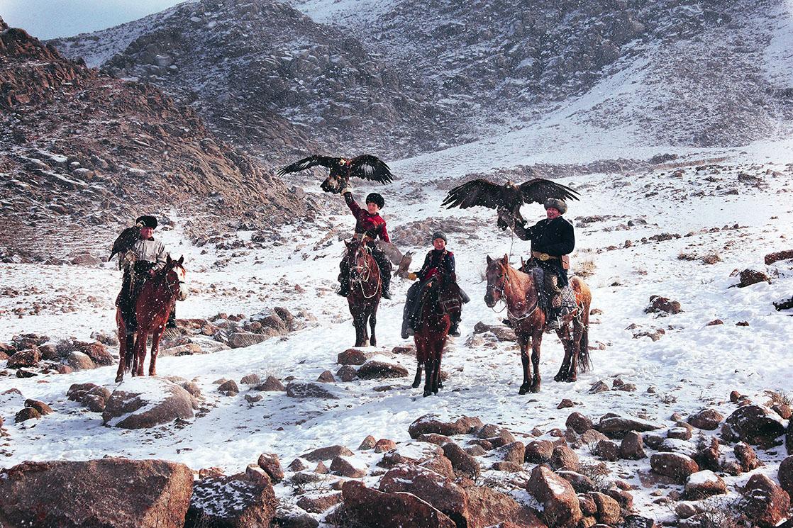 Scènes de chasse pendant l'hiver au Kirghizistan. A Bokonbayevo, il fait moins 25 degrés, mais les aigliers traquent quand même les loups et les renards. Chasseurs de génération en génération, les plus jeunes suivent leurs pères un faucon à bout de bras. On aperçoit, Azim, fier du haut de ses 10 ans malgré le froid. A sa gauche, son père Talgarbek, 39 ans, porte Toumara, un aigle femelle de quasiment deux mètres d'envergure | KIRGHIZISTAN