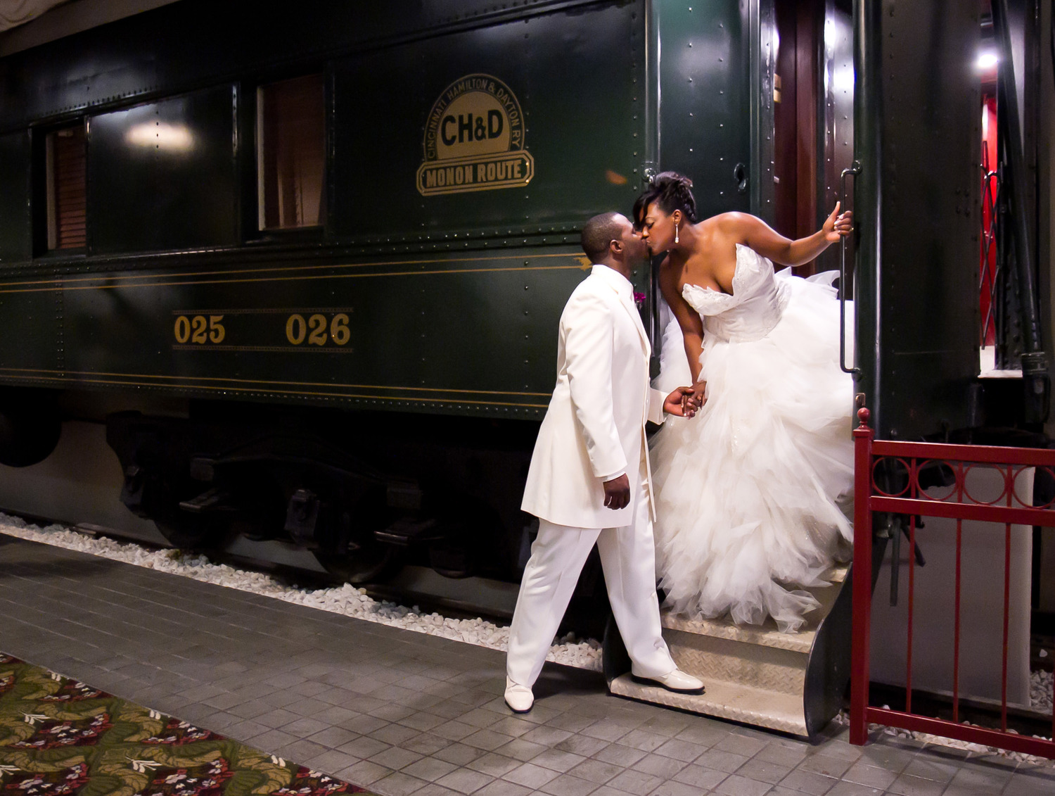 Photograph of a bride and groom kissing in front of a train