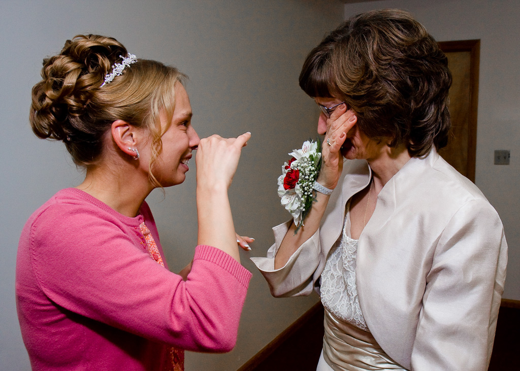 Candid photograph of a bride and her mother crying