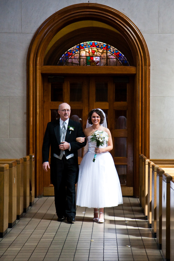 Photograph of a bride and her father walking down the isle in a church