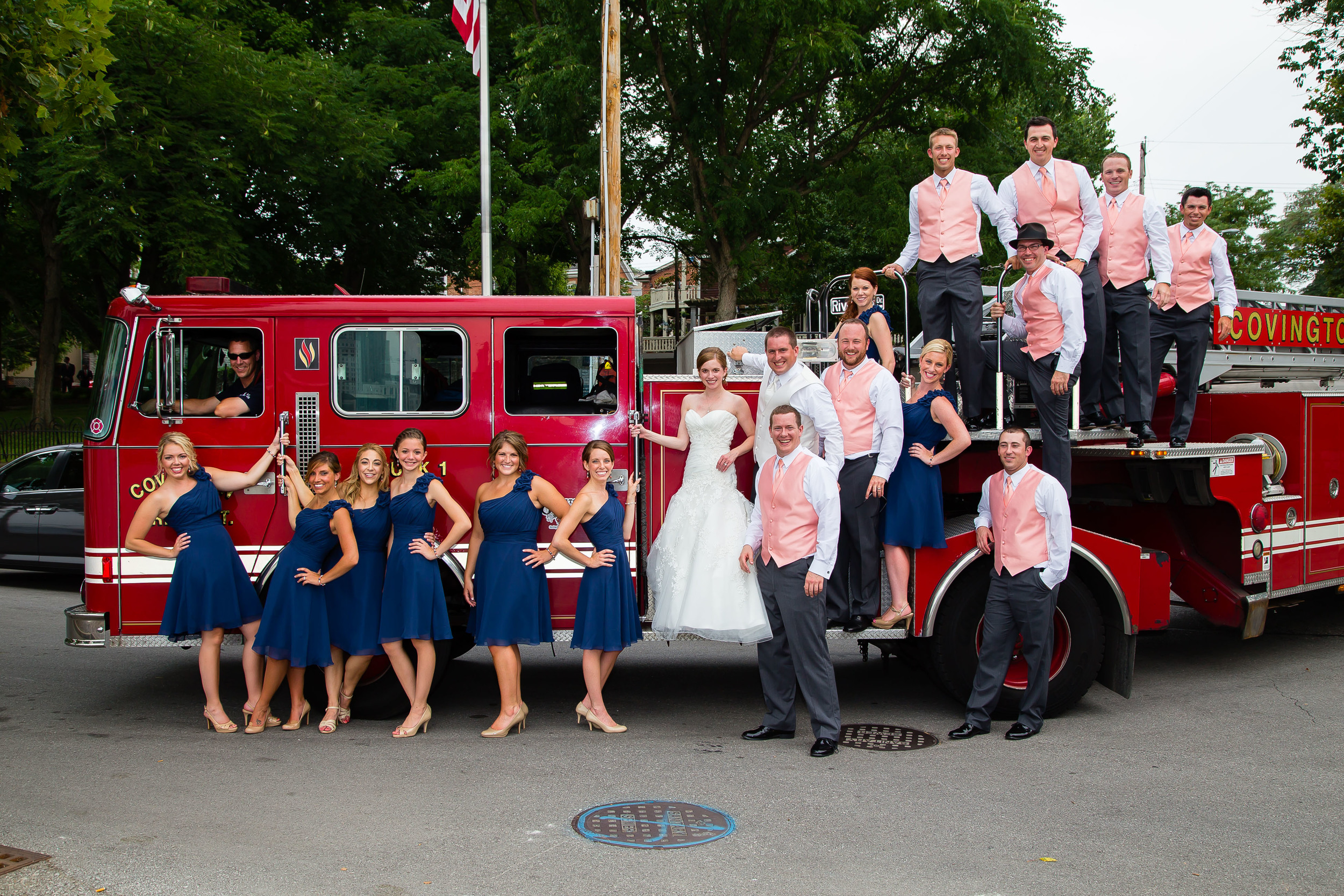 Wedding photograph of a bride and groom with wedding party in front of a fire truck