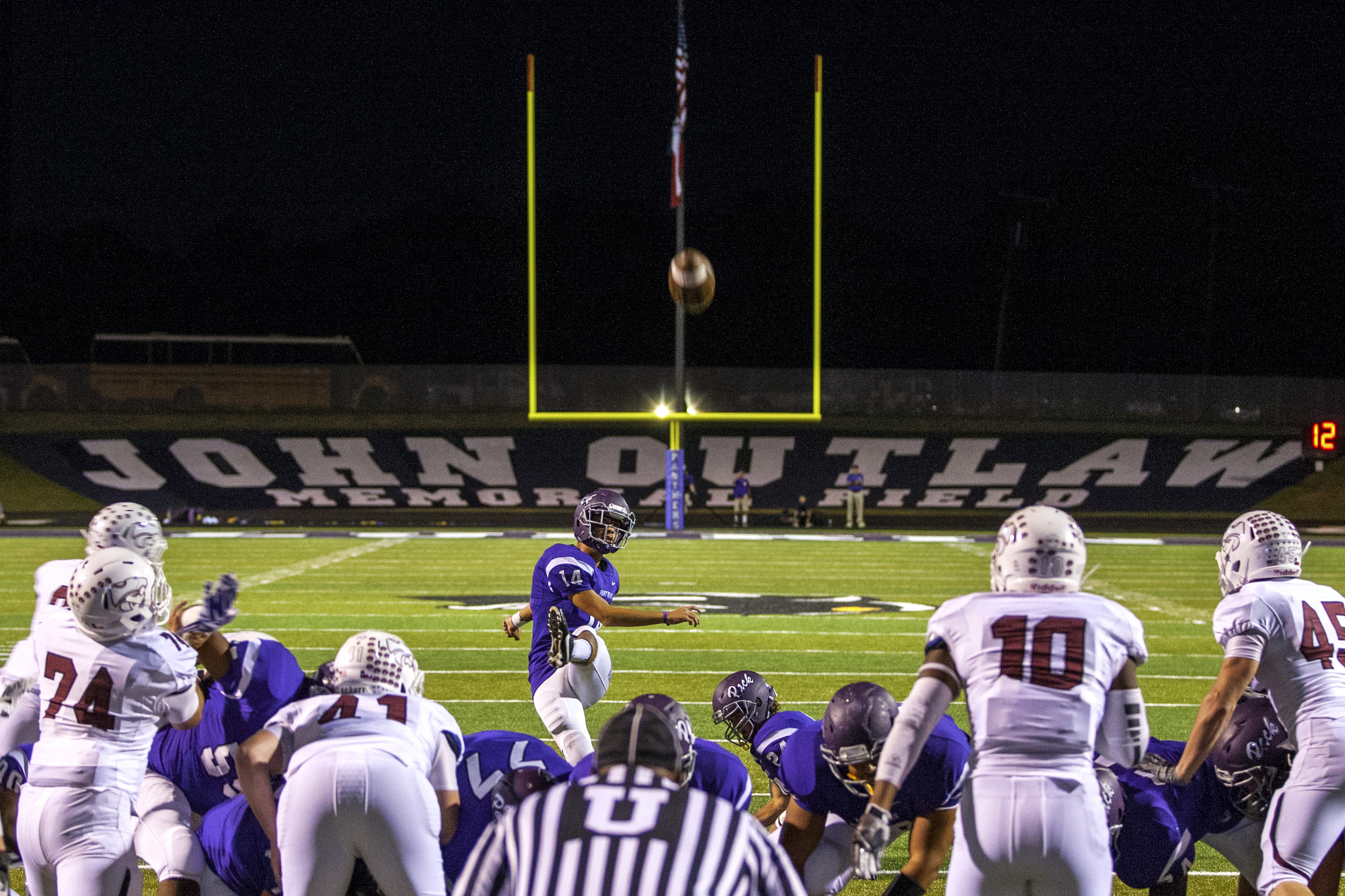 Lufkin High School kicker Javier Montes (14) converts a point-after-touchdown during first quarter action of the Pack's homecoming football game against Whitehouse played on Oct. 3, 2014 at Abe Martin Stadium in Lufkin, Texas. Lufkin was rocked in late 2011 when it received the news that John Outlaw, its head coach for 17 years, passed away after a heart attack. Soon after, the Panther community dedicated its playing field to head coach John Outlaw, and since 2012 the Pack has played its games at John Outlaw Memorial Field at Abe Martin Stadium. Outlaw's legacy at Lufkin includes over 160 games won, three trips to the state semi-finals and a state championship victory in 2001.