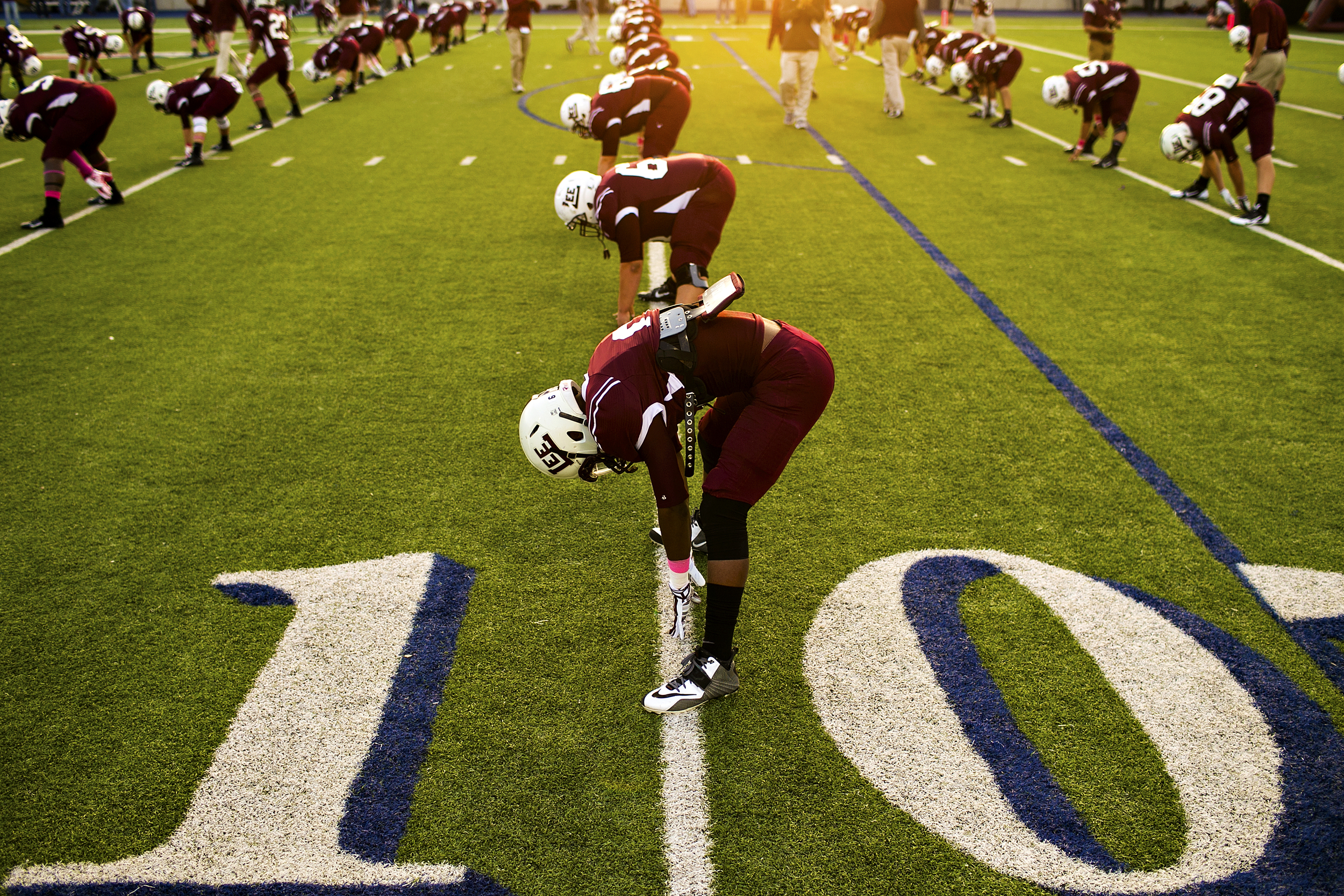 """Midland Lee senior defensive back Juwan Lee (6) and his teammates stretch prior to their rivalry game against the Odessa Permian Panthers on Oct. 12, 2014 at Grande Communications Stadium in Midland, Texas. The Panthers beat the Rebels 45-28 in this year's installment of one of the most storied rivalries in high school football nationwide. While the rivalry is renowned for being a central point in H. G. Bissinger's book, and subsequent movie, """"Friday Night Lights,"""" the Permian-Lee game raised to national prominence after a 20-year stretch from 1980 to 2000 in which both schools were in the running for the state championship seemingly every year. During that stretch, Permian won the title four times, with Lee claiming three championships and each school claiming a national championship title. Although both schools are far removed from their heyday as perennial state contenders, the annual game still draws over ten thousand attendees every year and is the most important game in both teams' schedules."""