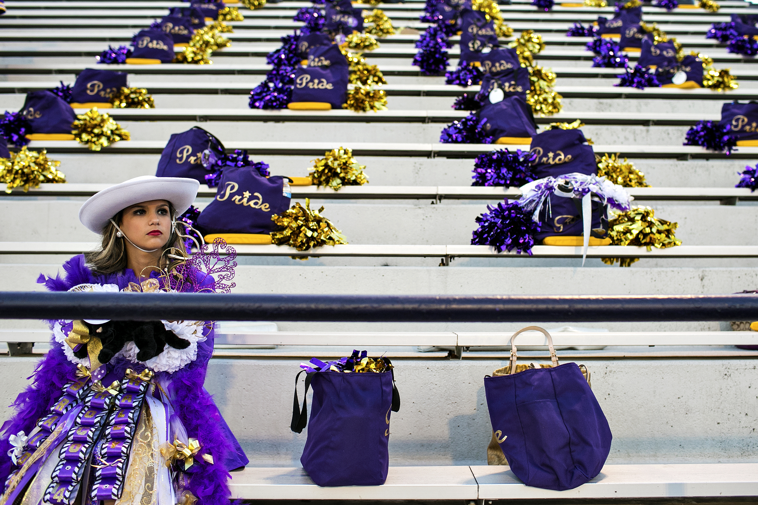 """A member of Lufkin High School's """"Panther Pride"""" drill team sits in the empty stands prior to the Panther's homecoming football game against Whitehouse played on Oct. 3, 2014 at Abe Martin Stadium in Lufkin, Texas. Established in 1905, Lufkin High has a proud football tradition dating back to the 1930s and '40s, when head coach Abe Martin led the Panthers to four district championships and only ten losses in seven years. The town's football success was continued by Dunbar High School, the segregated African-American high school in Lufkin, and its conquest of three state championship titles in the 1960's. After Lufkin High's integration in 1970, the Panthers have continuously produced eventual NFL players, including current Dallas Cowboys star Dez Bryant, and were crowned state champions in 2001."""