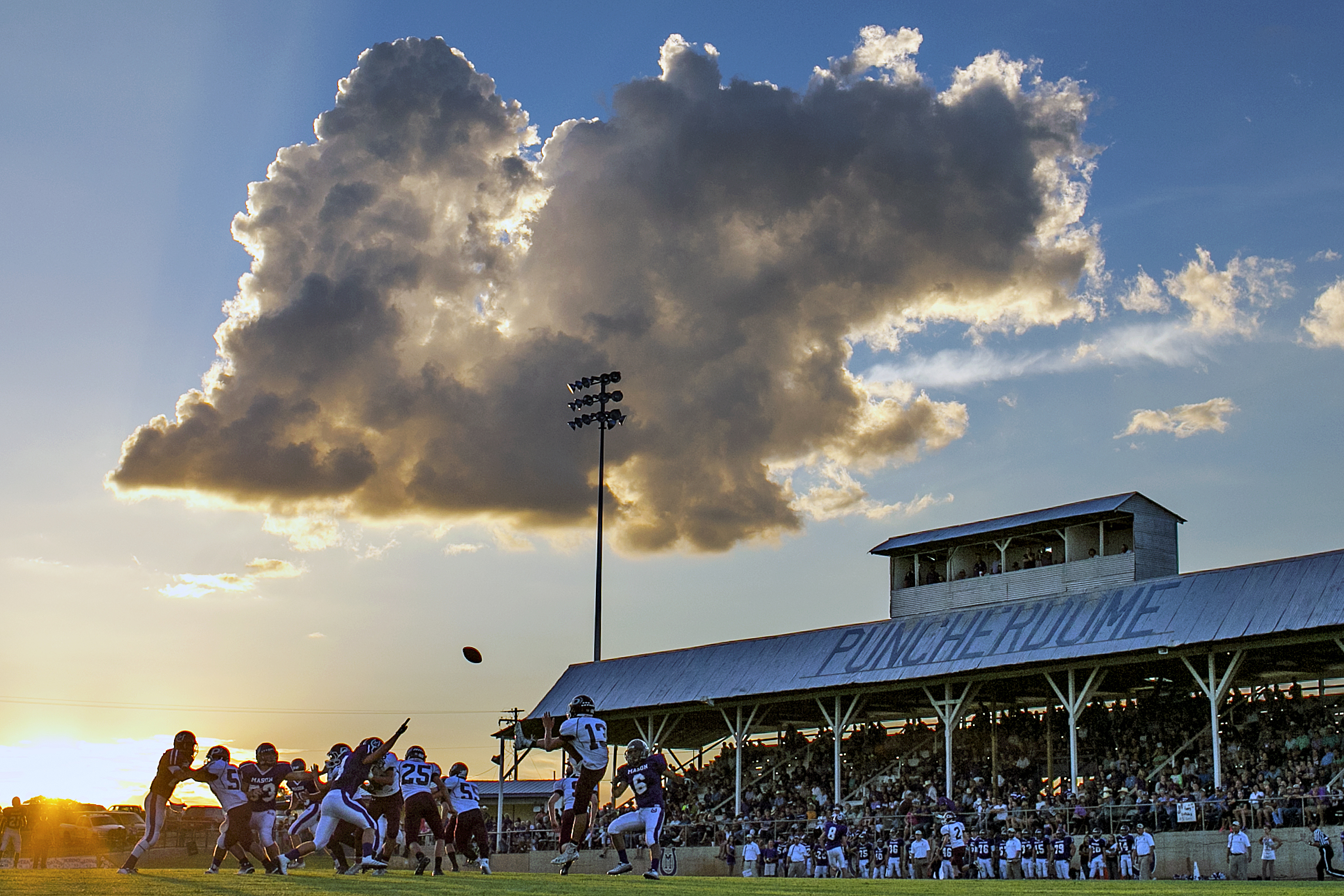 """The De Leon Bearcats are forced to punt as the sun sets on The Puncher Dome during their Week 2 visit to Mason on September 5, 2014 at R. Clinton Schulze Stadium in Mason, Texas. Better known as """"The Puncher Dome,"""" Schulze Stadium was built in the late 1930's and originally used as a racetrack. It owes its nickname to the covered grandstands on the home side of the field. Home of the Mason Punchers, a 2A school with just under 200 enrolled students, The Puncher Dome has been witness to over 70 seasons of Puncher football, with its most successful one being the state championship campaign of 2011."""