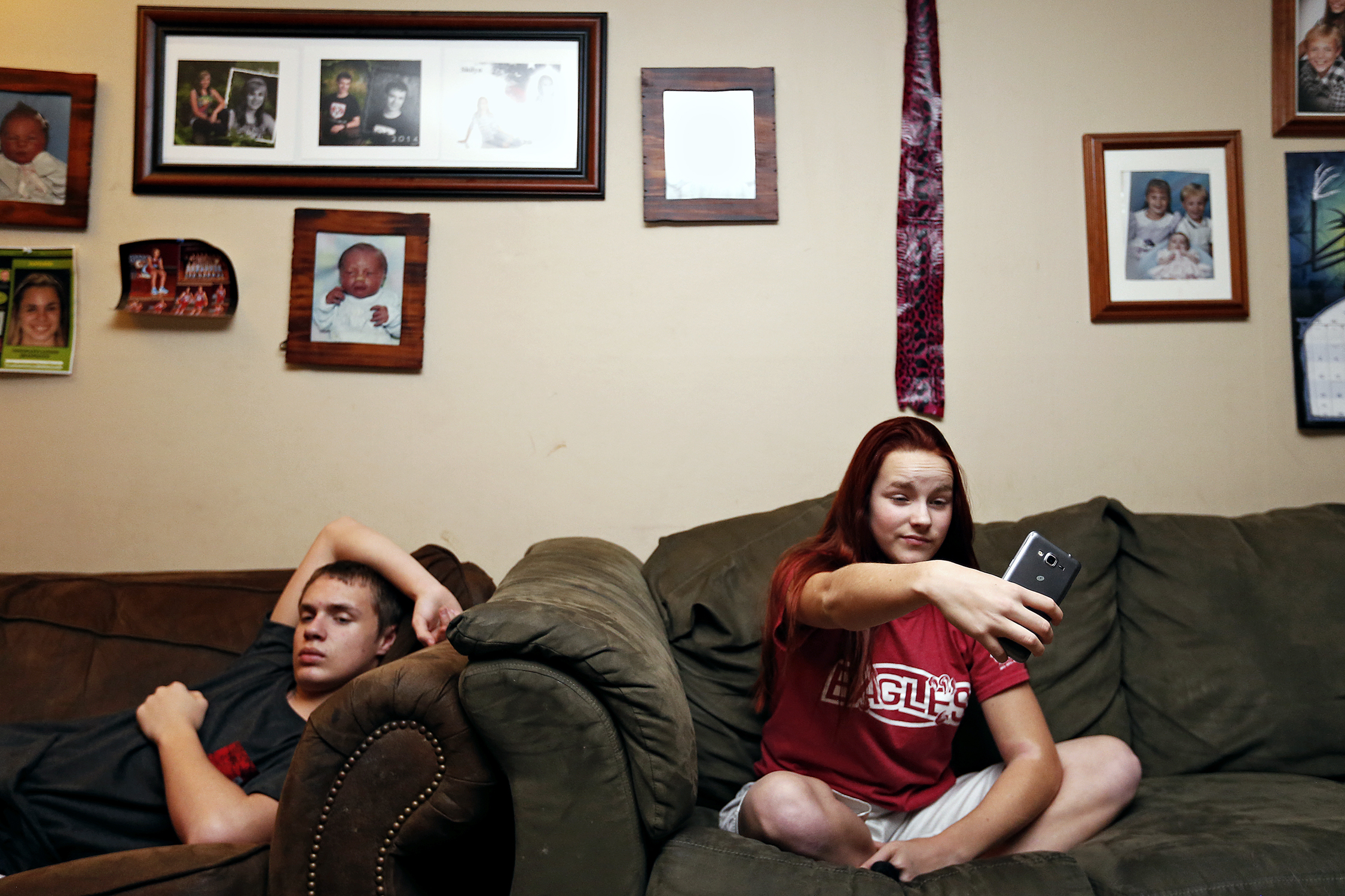Shilyn Bradt takes a selfie while her brother Chance watches television at their home in Springfield, Mo. on Feb. 9, 2016.