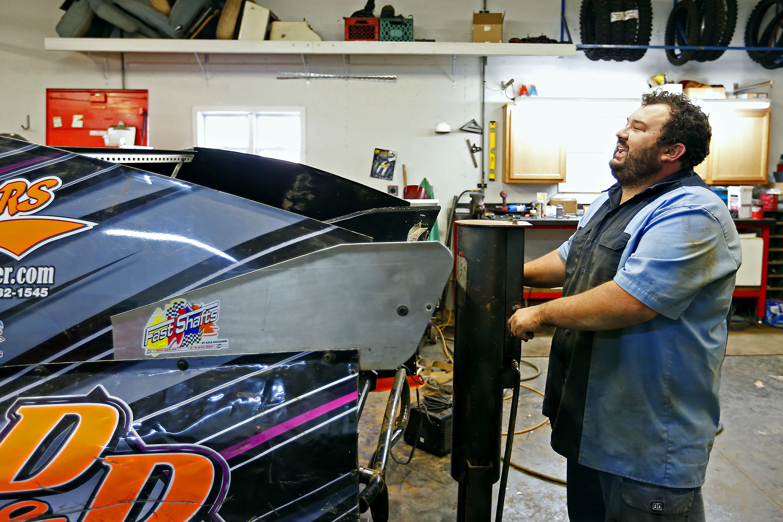 Mickey Burrell laughs as he and Elston Moore put the finishing touches on Burrell's car before heading to race at Springfield Raceway in Springfield, Mo. on July 25, 2015.