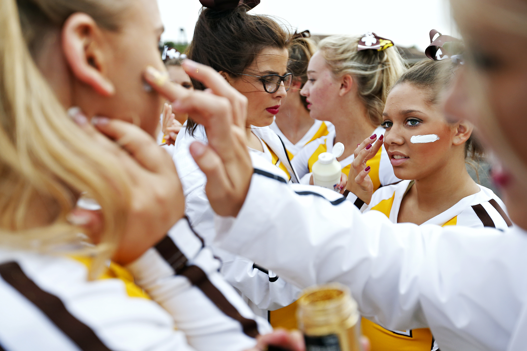 Kickapoo junior Alyssa Griffin (right) gets her face painted by fellow cheerleader Josie Neal prior to the Chiefs' season opener against the Parkview Vikings at Kickapoo Chiefs Stadium in Springfield, Mo. on Aug. 21, 2015.