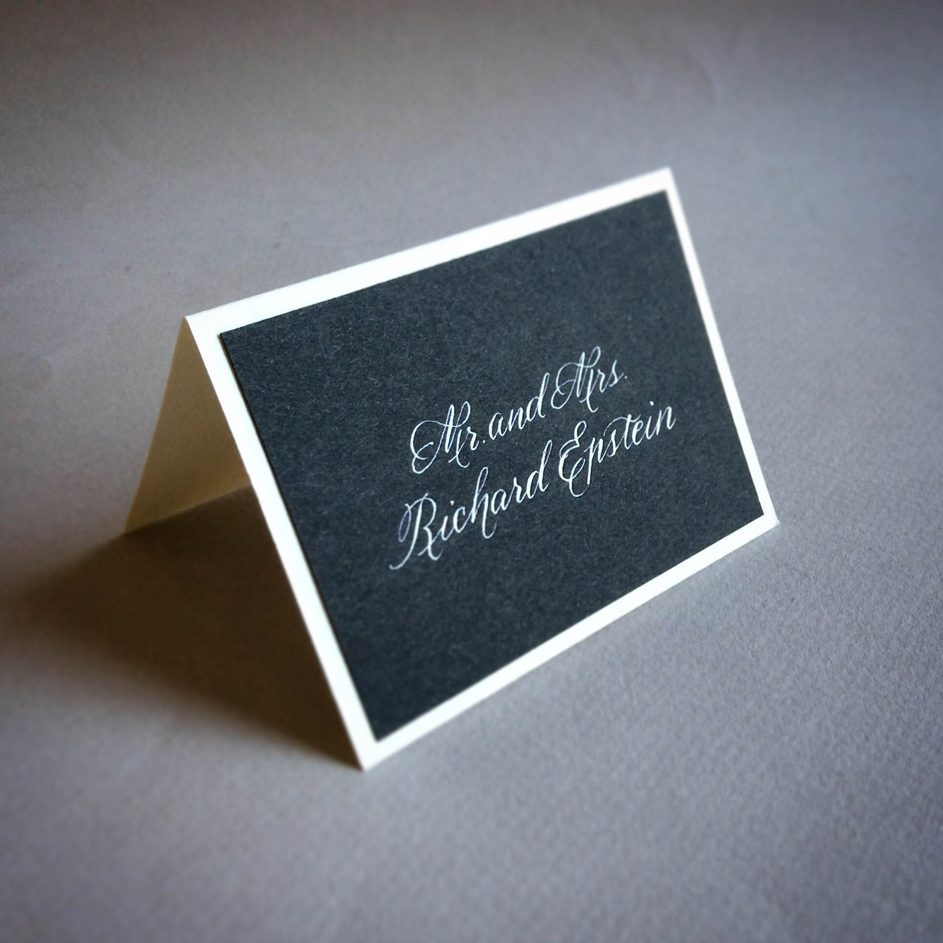 Custom escort card with opaque white calligraphy.