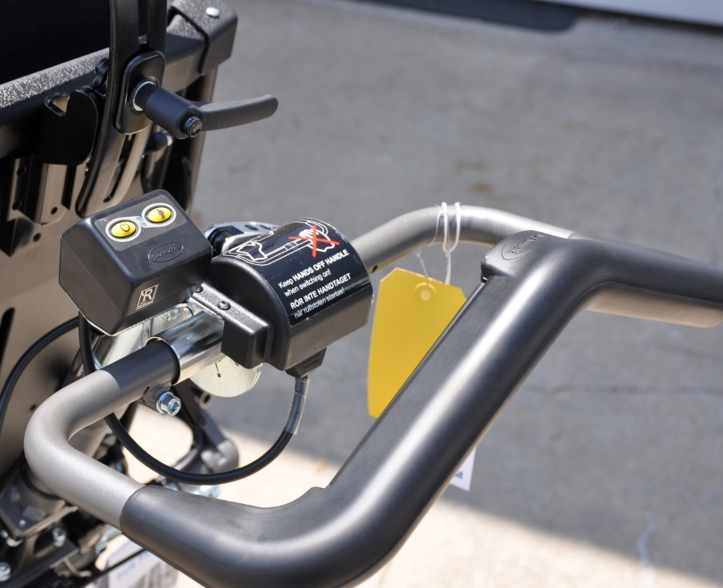 Permobil pressure-sensitive push handle replacing the traditional attendant joystick.