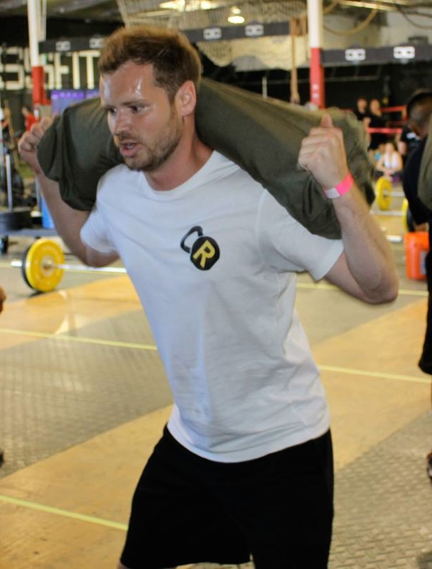 Jake crushing sandbag back squats at the Deadly Duos competition