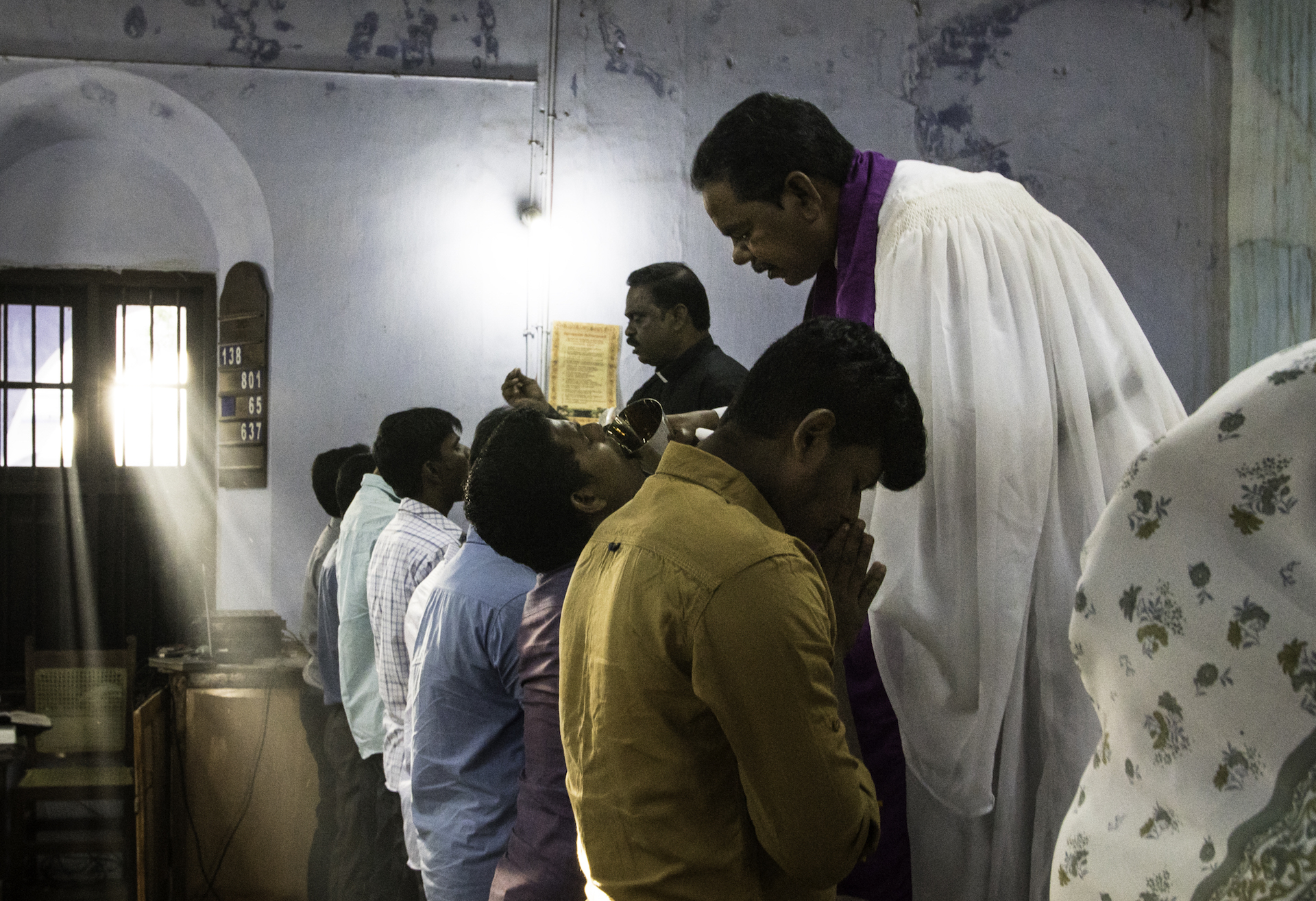 Rev. Christu Das, Principal of CTSN, distributes the Lord's Supper during weekly Divine Service at CTSN.Johanna Heidorn, photographer