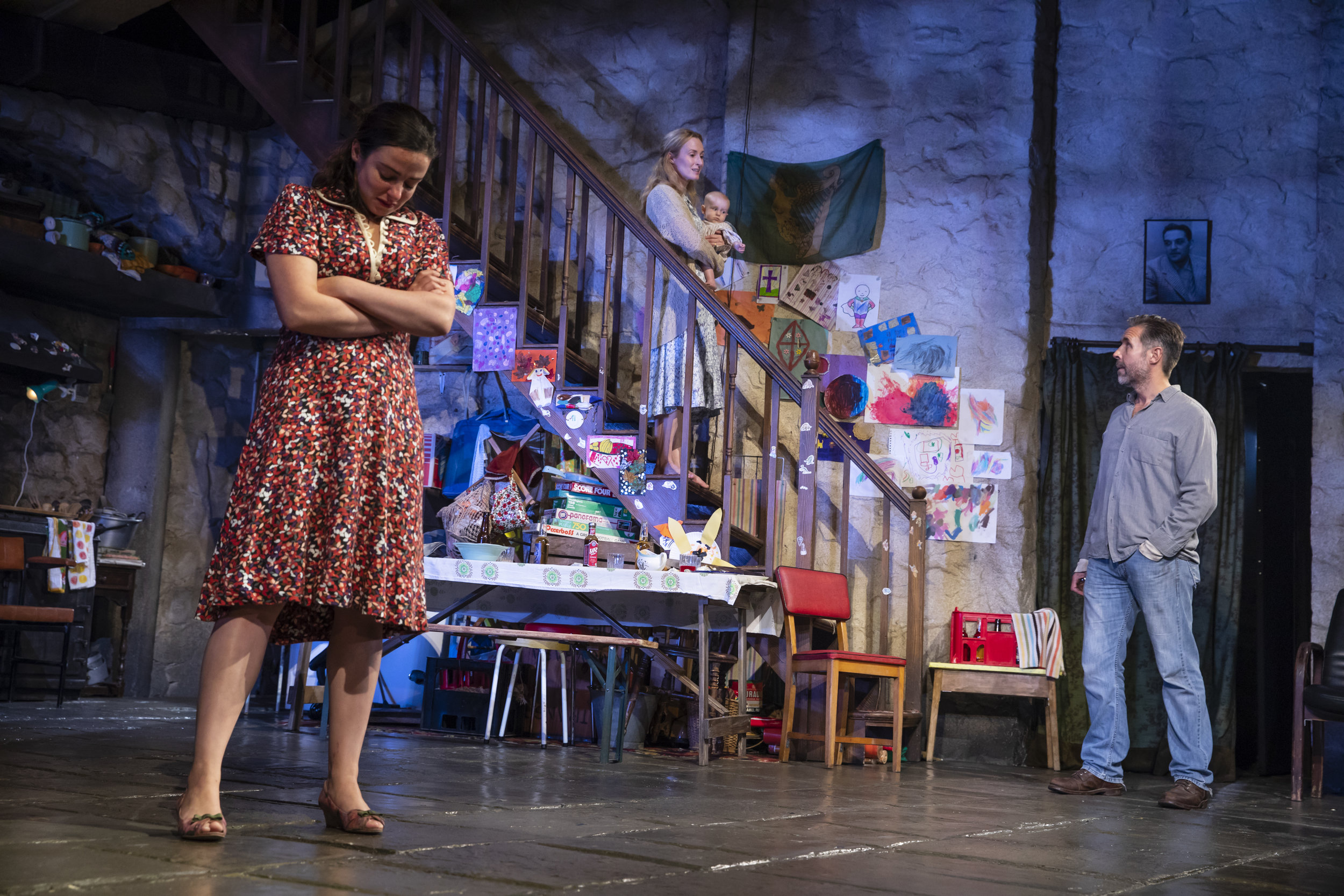 The Auld Triangle. Mary (Genevieve O'Reilly) and newest child, nine-month-old Bobby, implore Quinn (Paddy Considine) to call it a night while Caitlin (Laura Donnelly) waits. Photo by Joan Marcus.