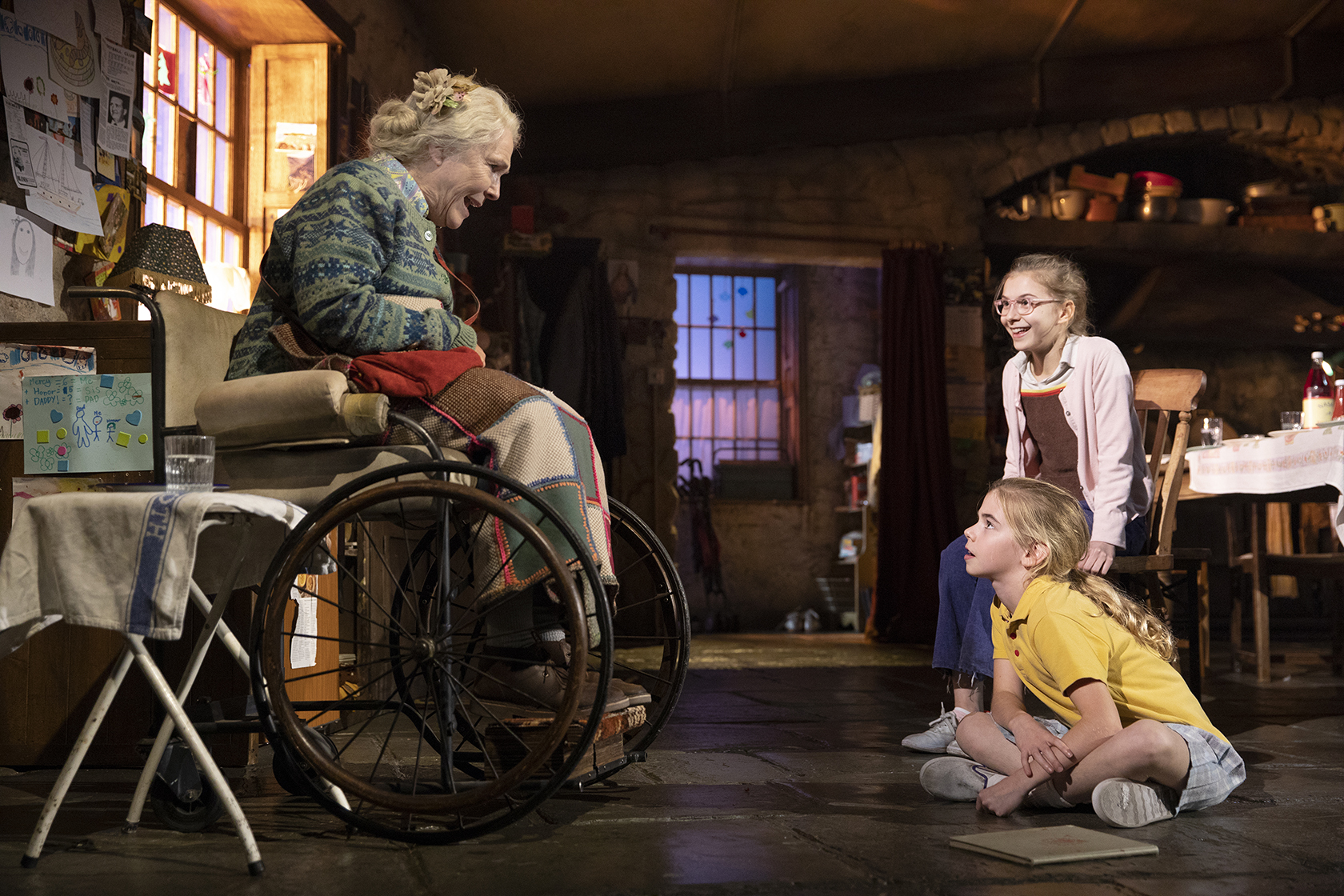 """When """"Aunt Maggie Far Away"""" (Fionnula Flanagan) comes back, her nieces pull up a chair. On floor, Matilda Lawler as Honor Carney (7). In chair, Brooklyn Shuck as Nunu Carney ( 11) . Photo by Joan Marcus."""