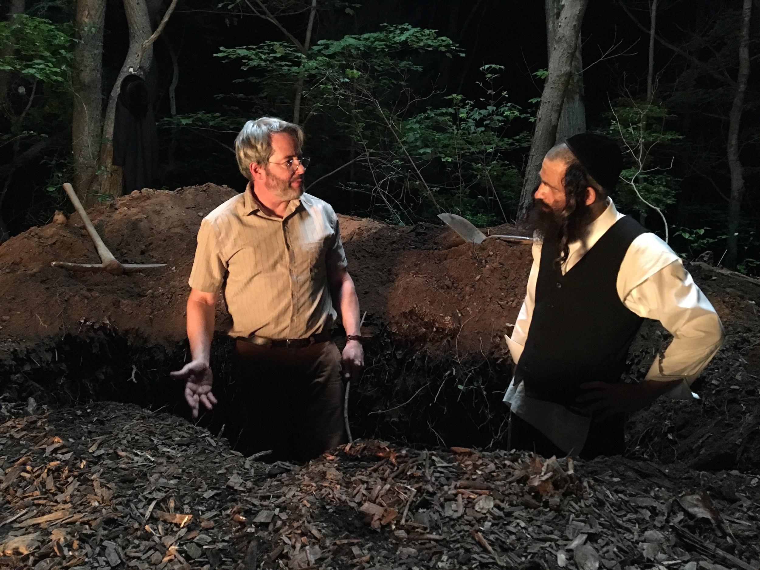 Matthew Broderick as Albert, a community college science teacher, and Géza Röhrig as Shmuel, a widowed Hasidic cantor, deliberating in their pig grave.