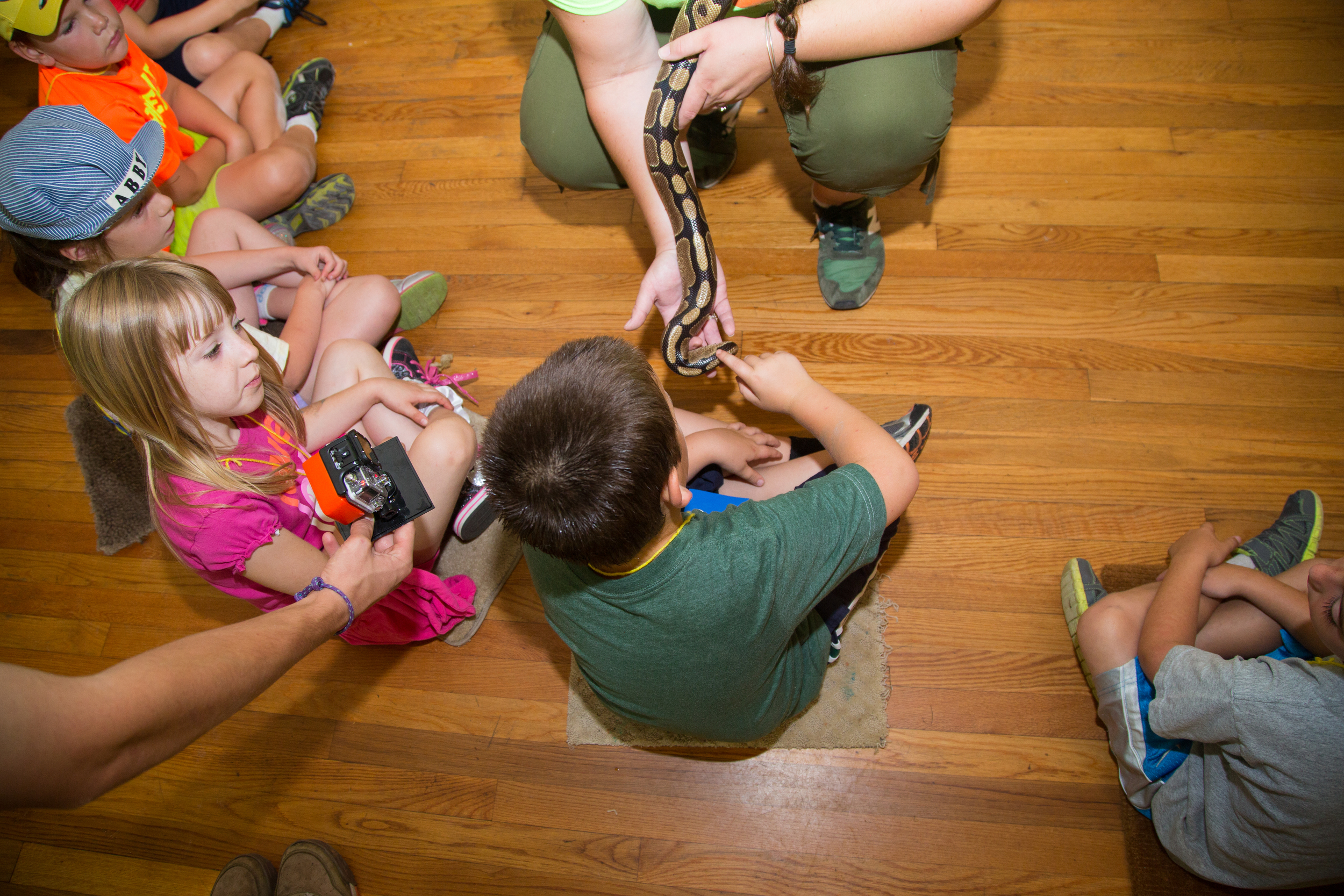 Students touch a huge snake while a counselor documents at Woodcock Nature Center.
