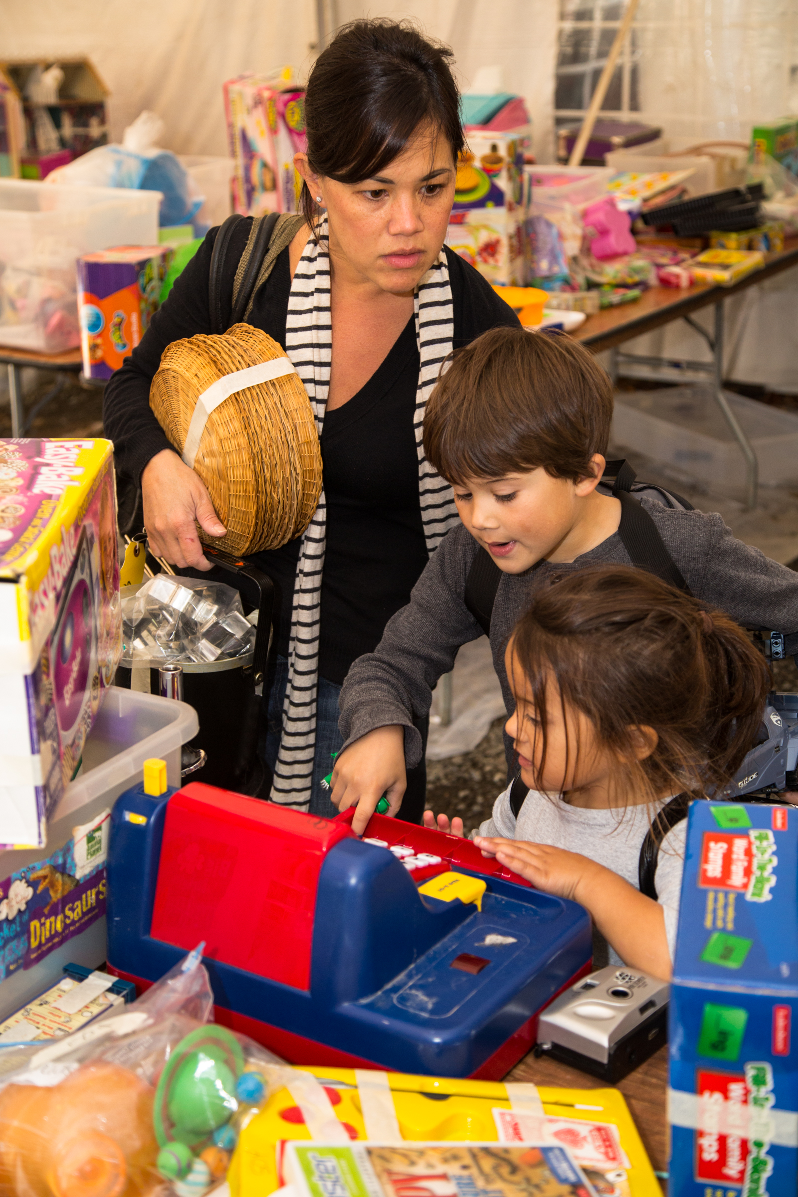 A frustrated mother shops with energetic children at an annual charity event.