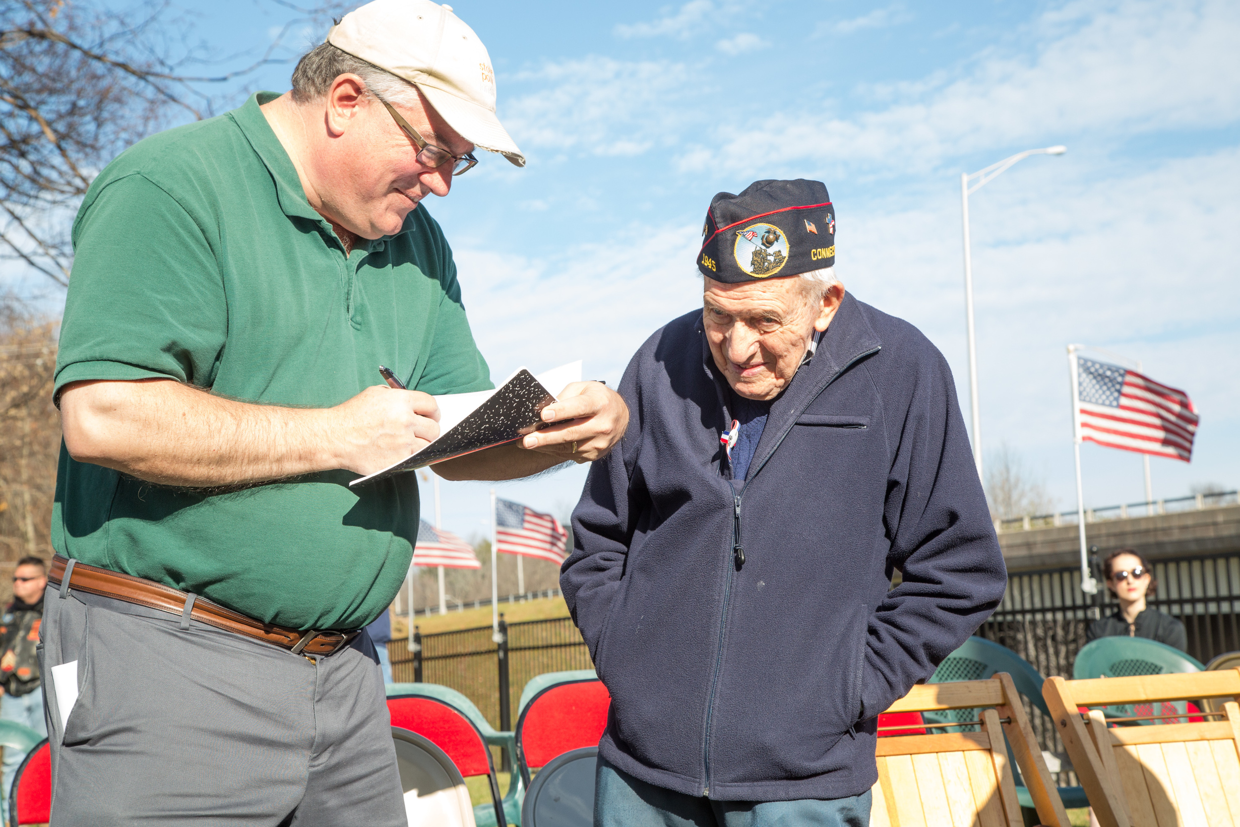 An Iwo Jima survivor speaks with a reporter at the New Britain Iwo Jima Memorial